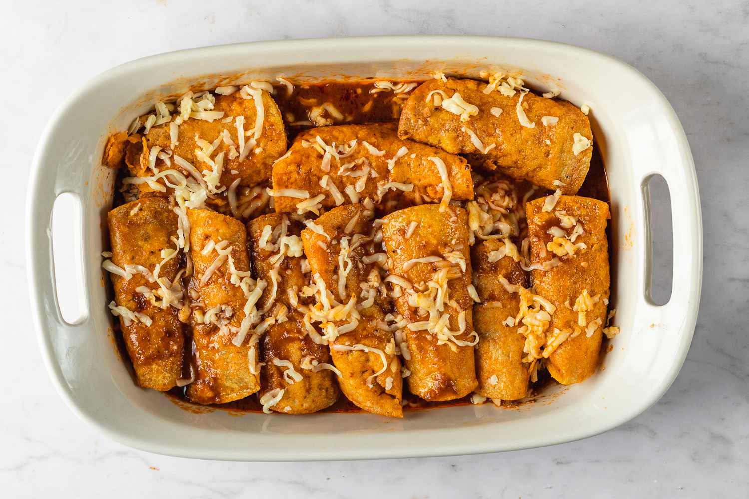 Pork Enchiladas in a baking dish with cheese on top