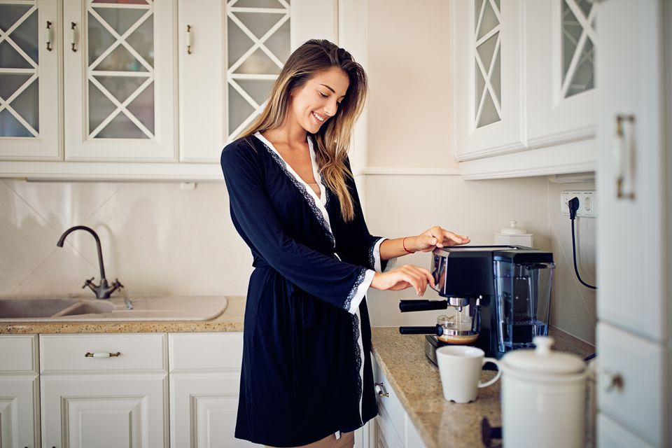 woman using cappuccino machine