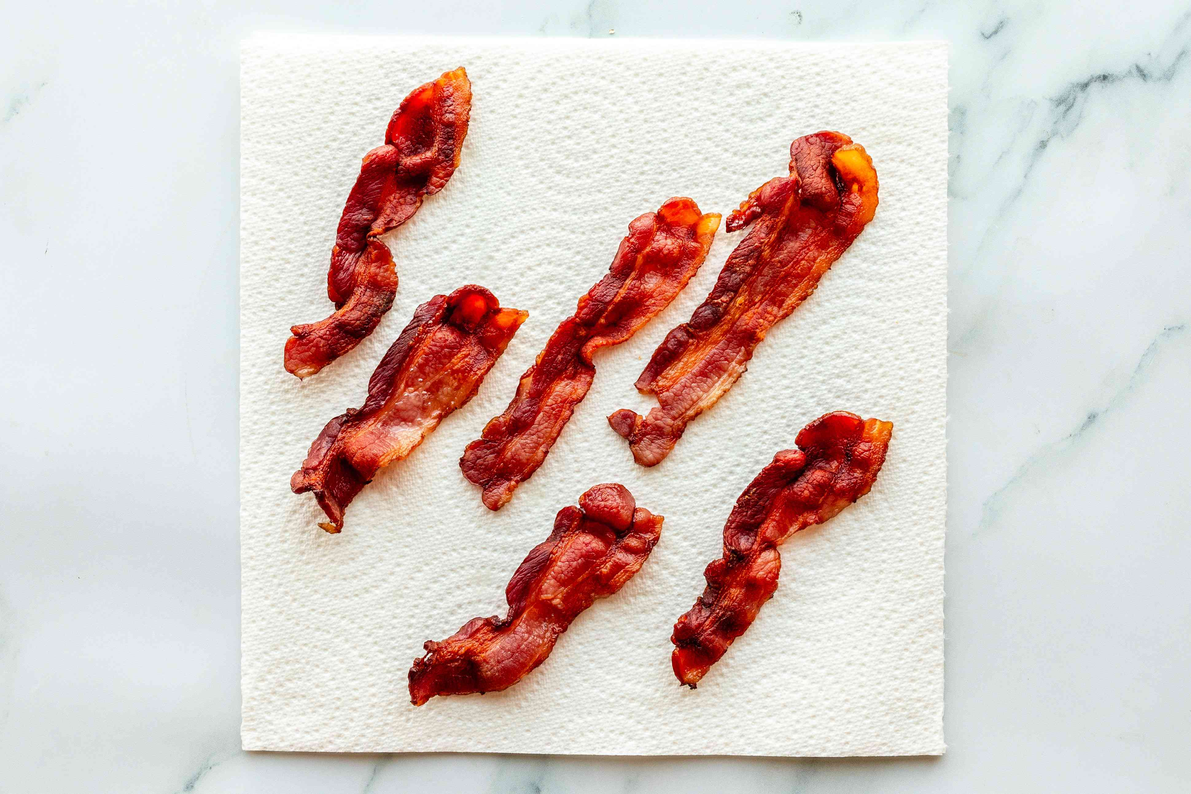 Six slices of microwaved bacon on a clean paper towel