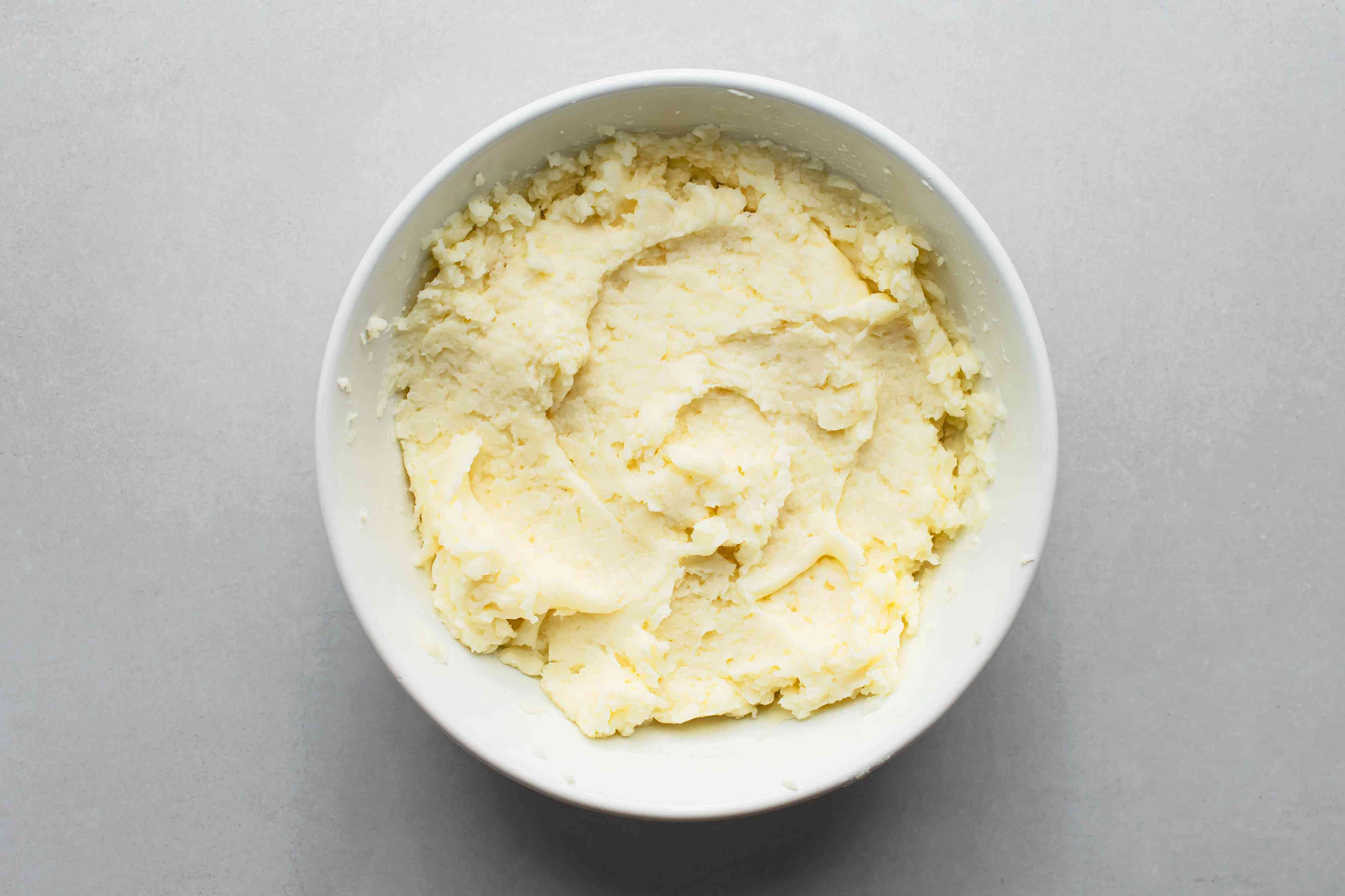 Cooked potatoes and butter mixture in a bowl