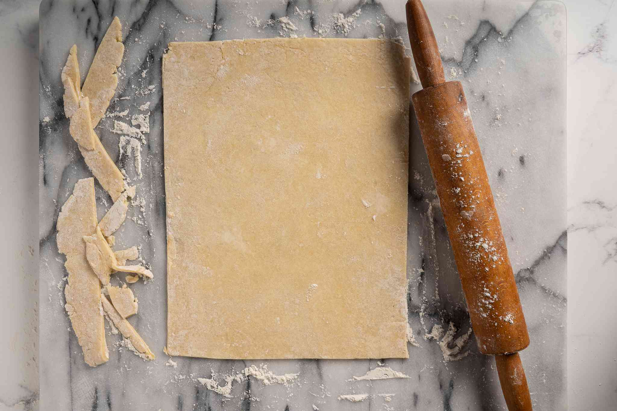 Pastry dough rolled out into a big rectangle on a floured surface
