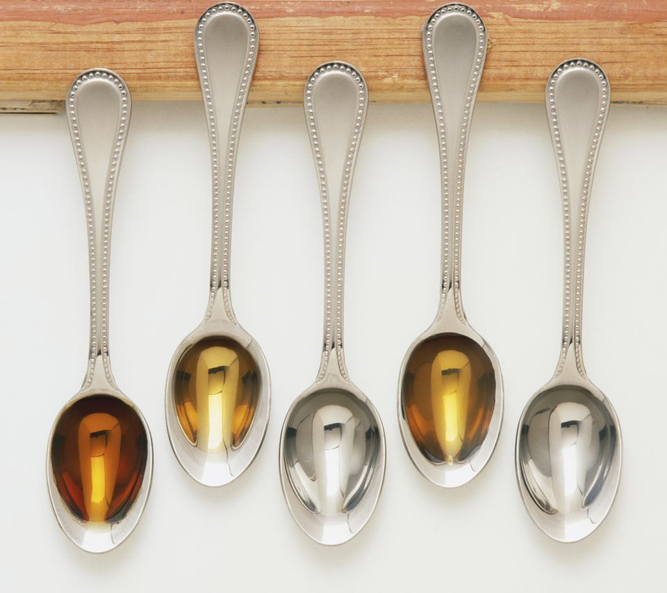 Liquid flavourings in five teaspoons, including dark rum, brandy, kirsch, vanilla extract and orange-flavoured water, view from above