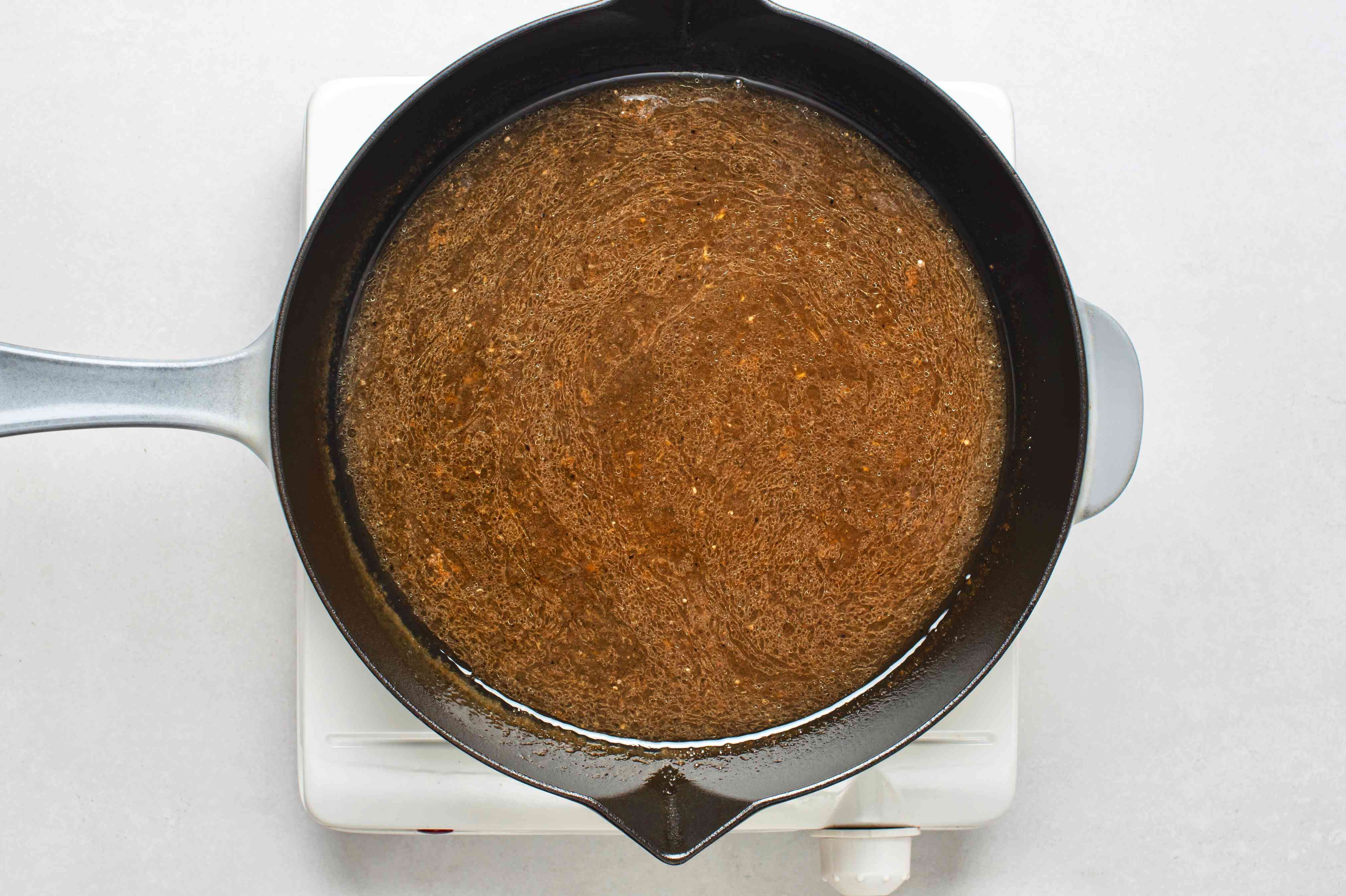 strained cooking liquid in a pan