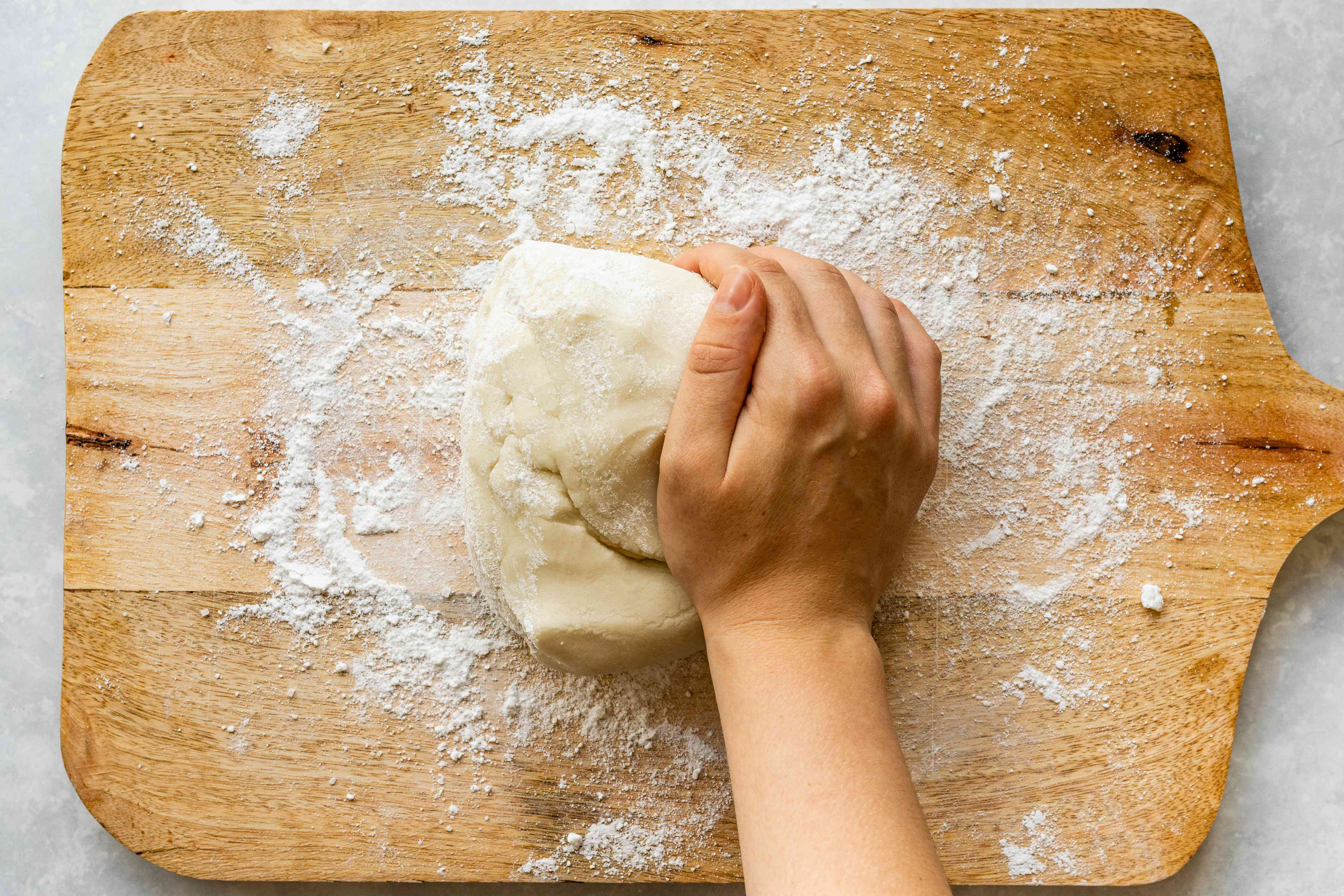 Kneading marzipan on a flour-dusted cutting board