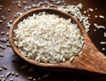 Close-up of raw rice in wooden spoon on table