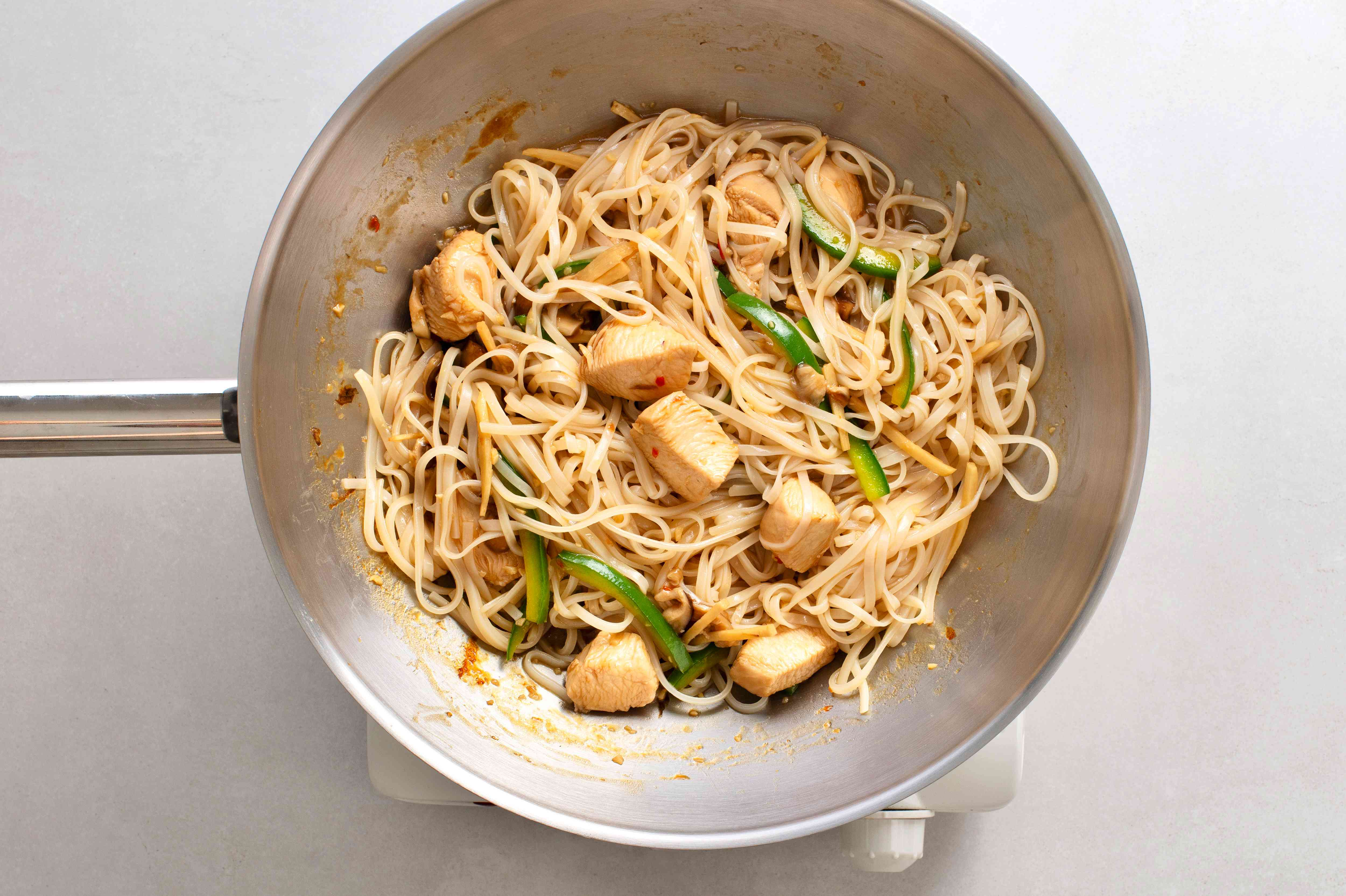 add rice noodles to the chicken and vegetables in a the pan