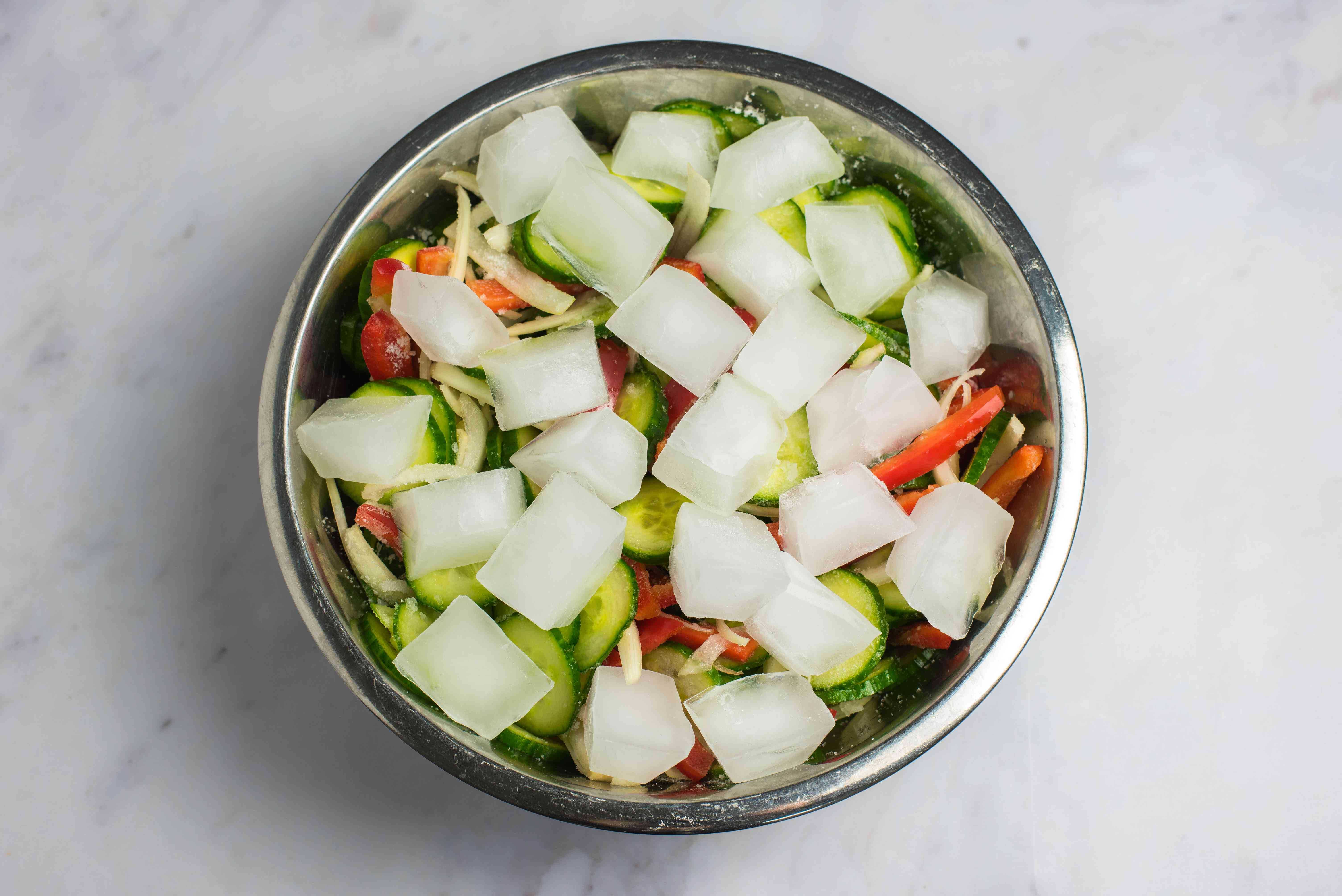 Place ice and cucumbers in stainless steel bowl