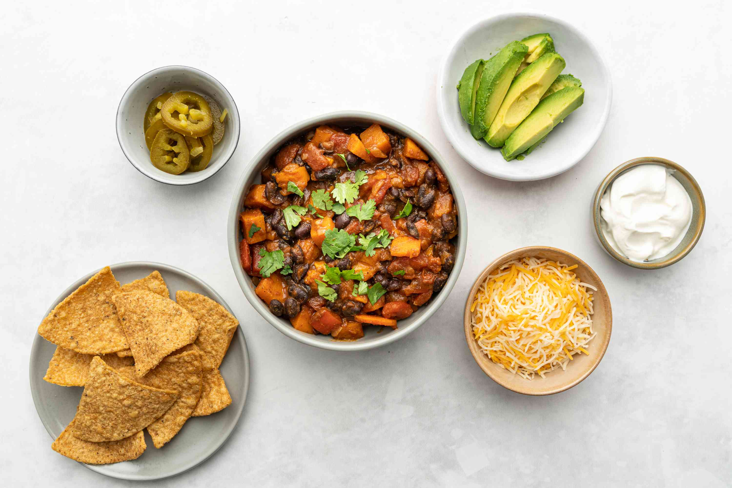 Black Bean and Sweet Potato Chili in a bowl, served with chips, cheese, sour cream, avocados and pickled jalapeños
