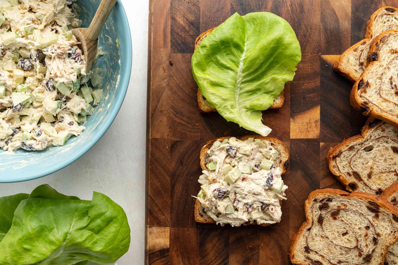 Chicken Waldorf sandwich on a cutting board; chicken salad in a bowl
