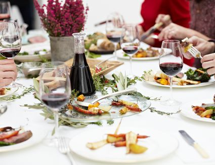 People sharing a meal and glasses filled with Pinot Noir