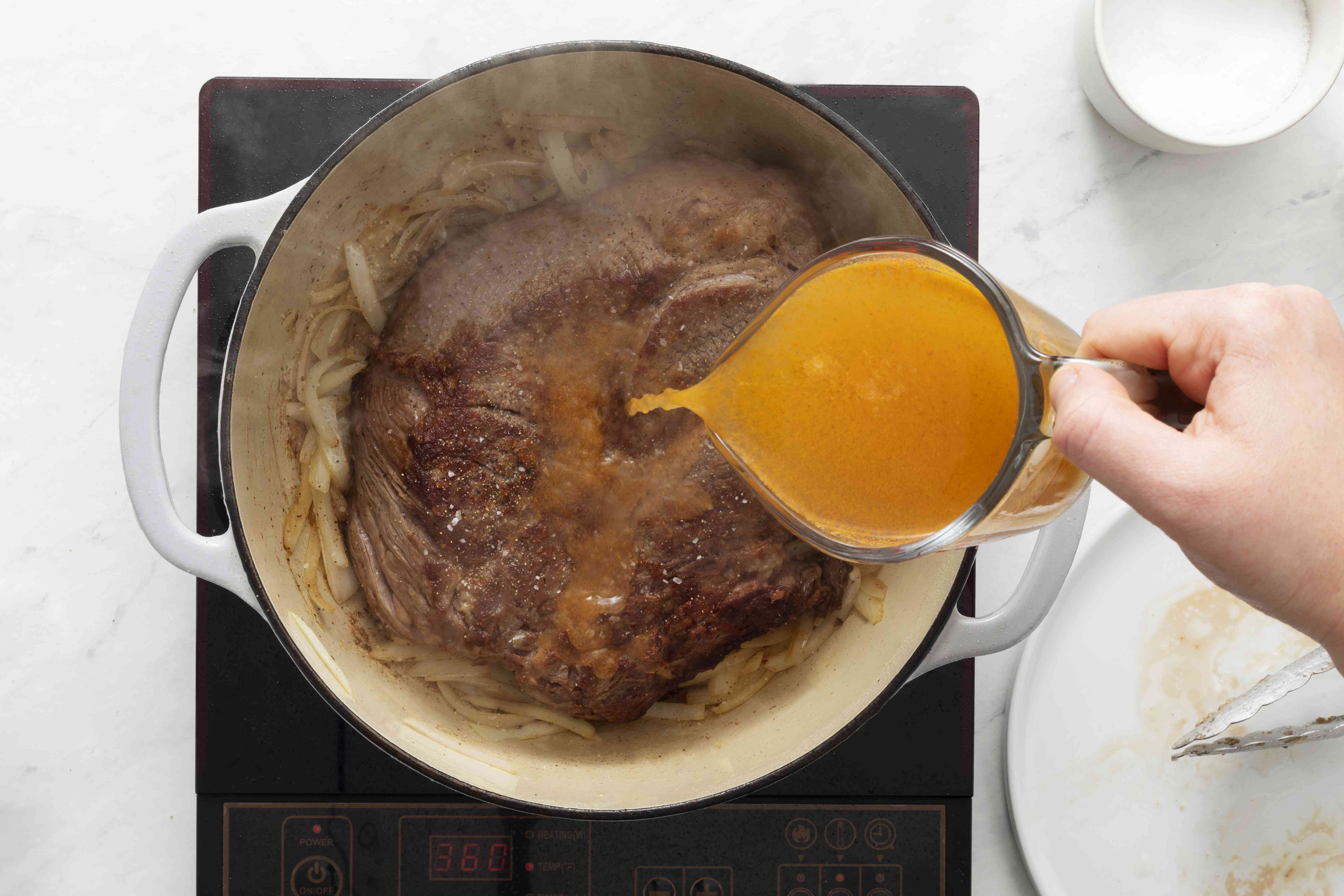 add pot roast and broth to the onions in the Dutch oven