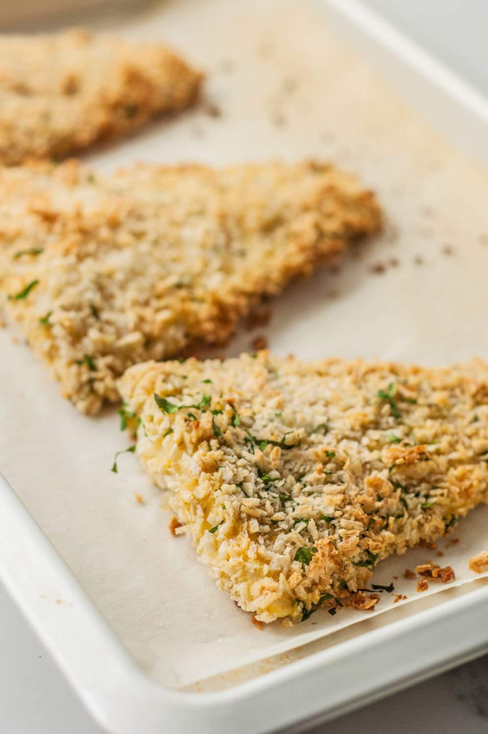 Panko-crusted baked fish on a rimmed baking sheet