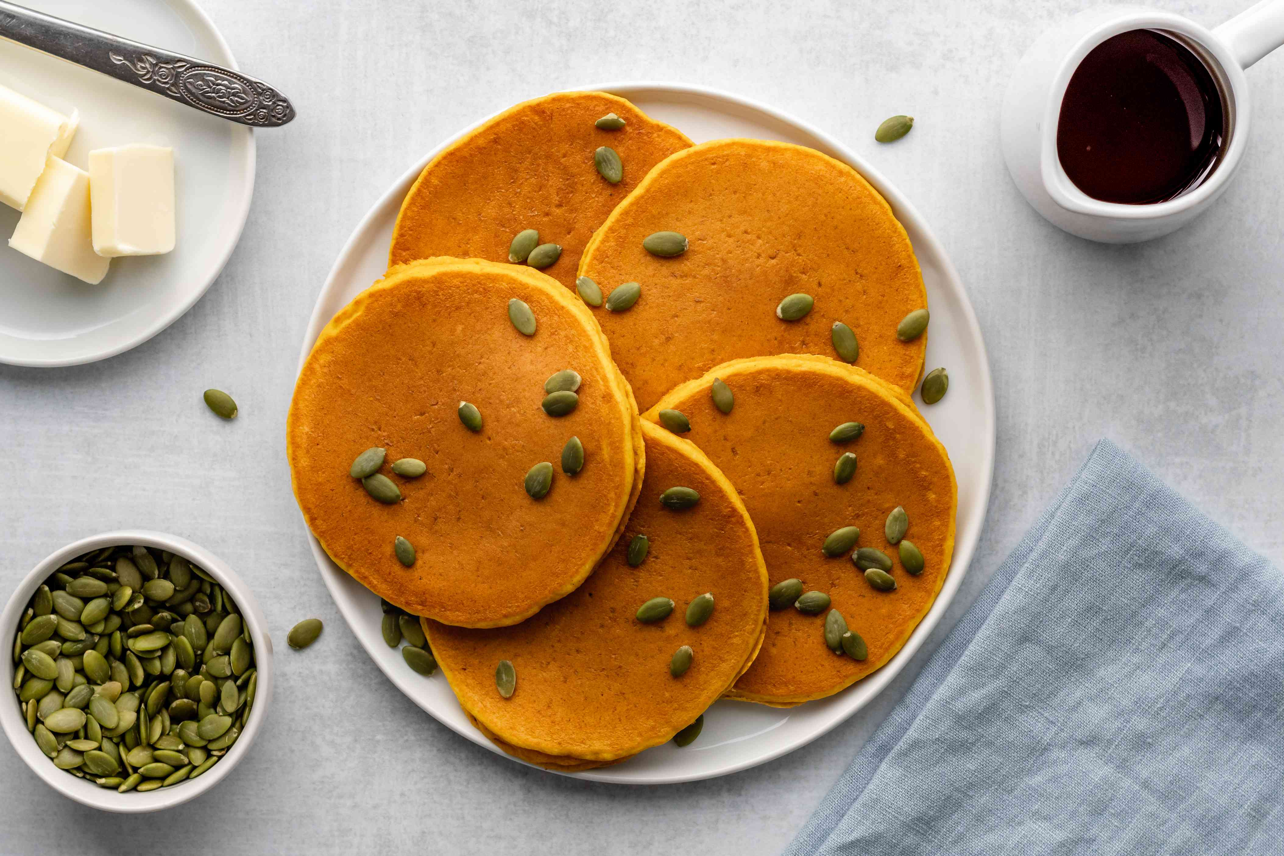 Quick and easy pumpkin pancakes on a plate, garnished with pumpkin seeds