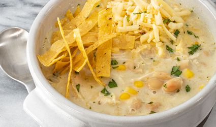 bowl of instant pot white chicken chili with tortilla strips and cheese