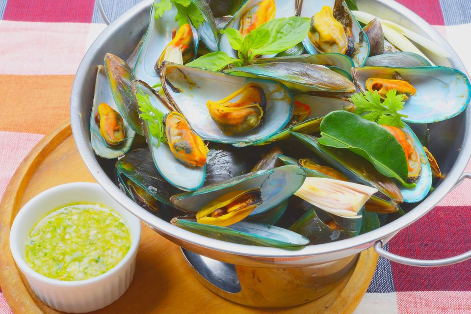 High angle view of thai mussels on a table with sauce on the side