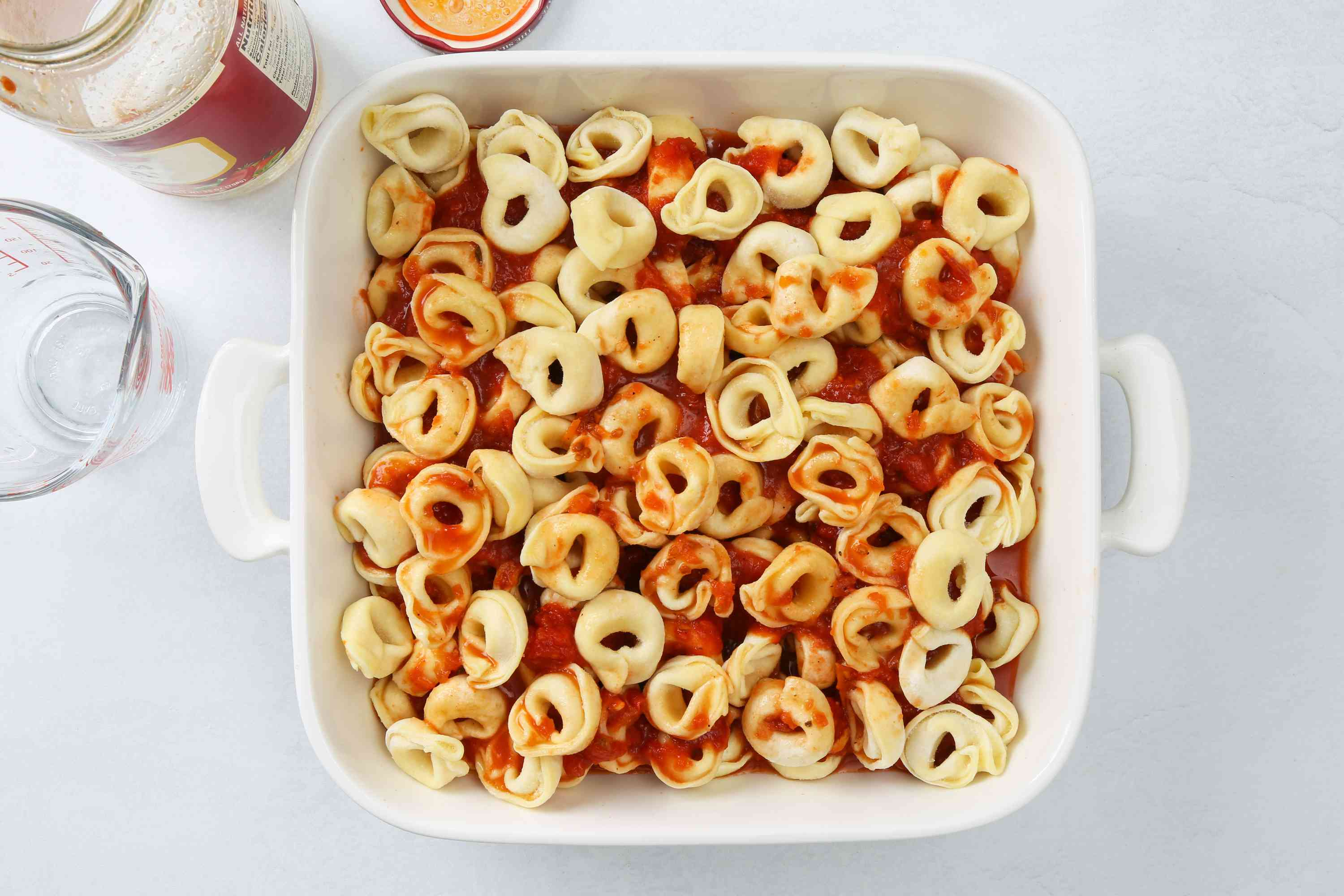 frozen tortellini and the spaghetti sauce in a baking dish