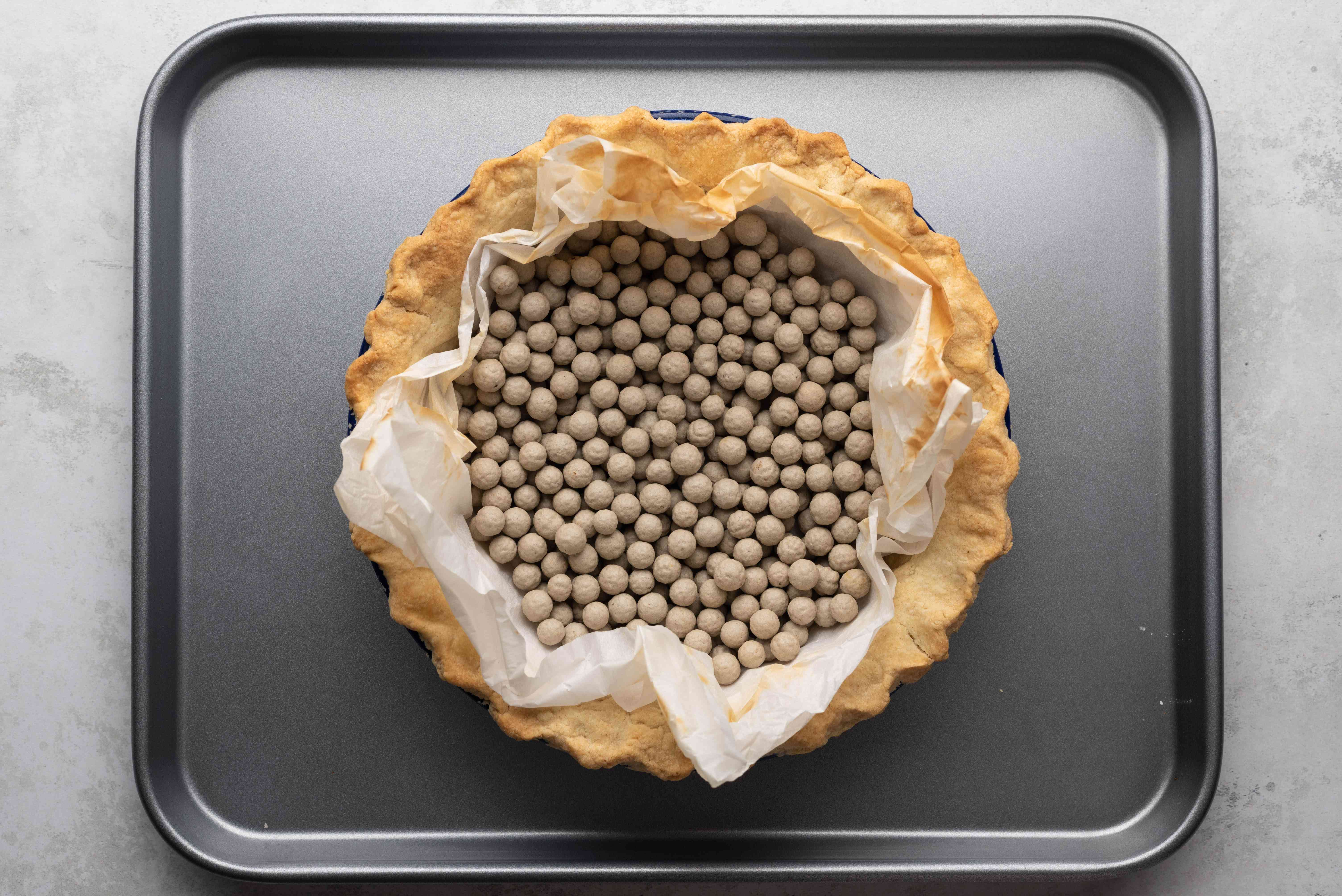 baked pie crust with pie weighting on a baking sheet
