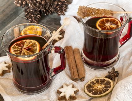 Glasses of mulled wine, orange slices and cinnamon stars on cloth and wooden tray
