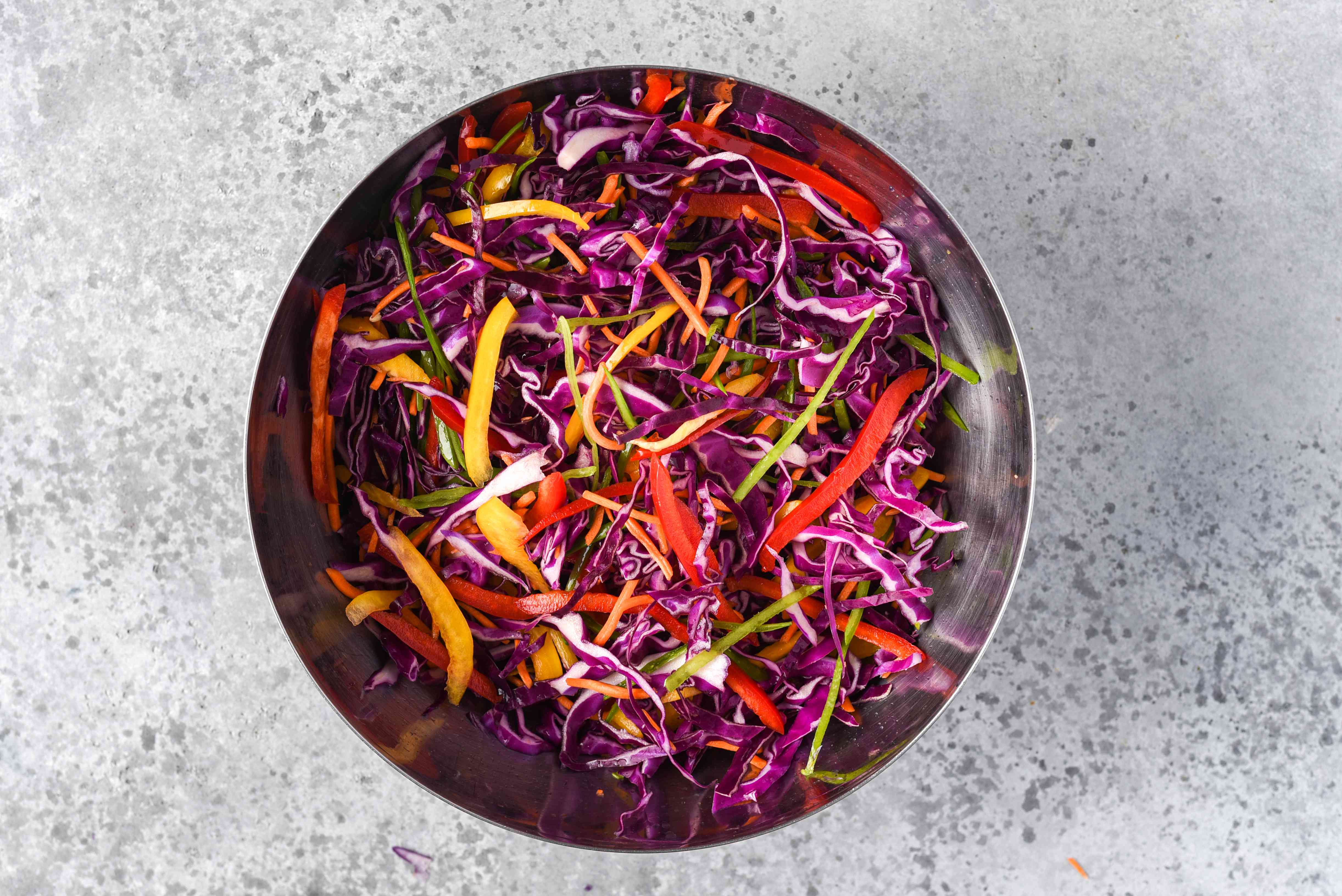 red and yellow pepper, carrots, and snow peas with the red cabbage in a bowl