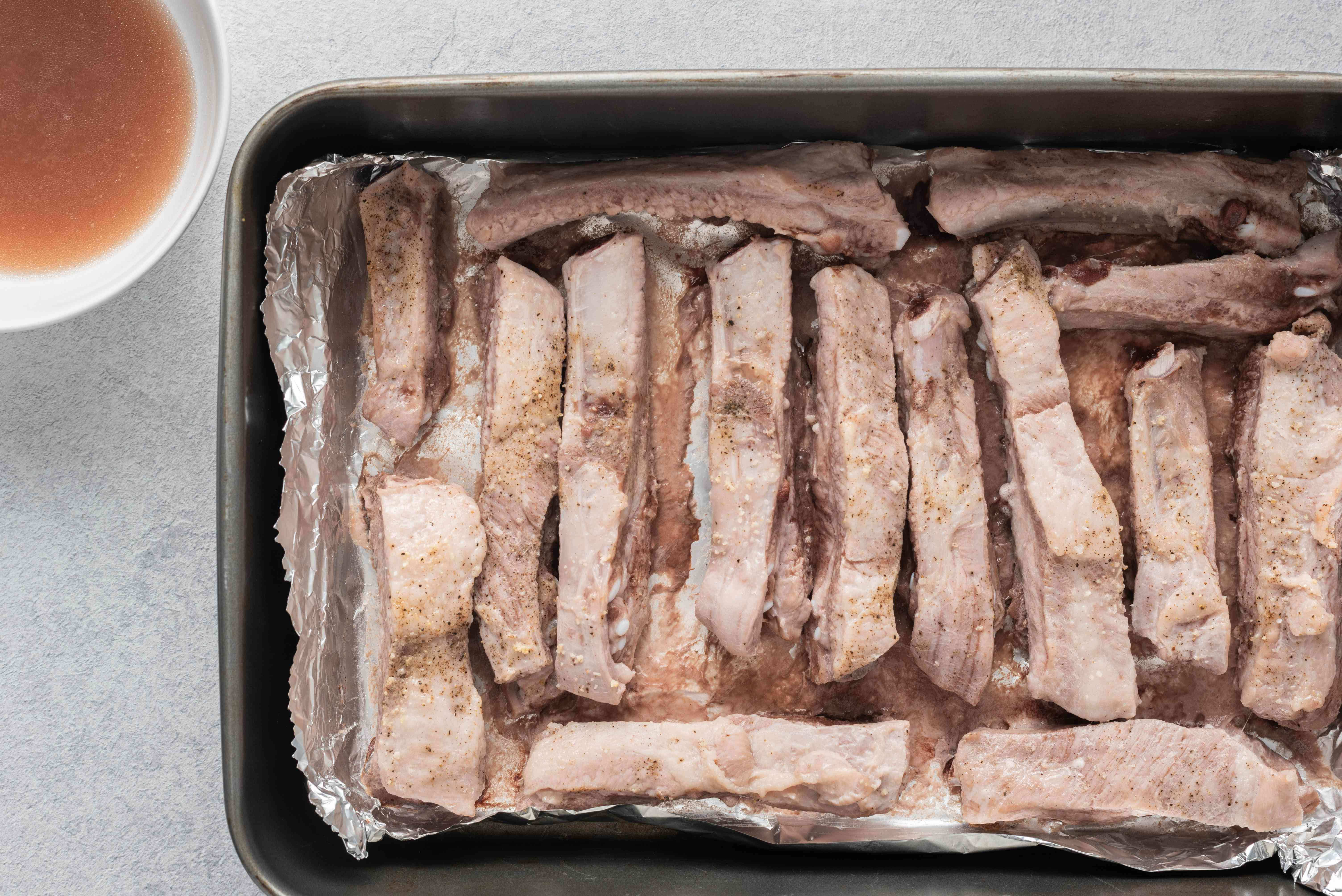 Ribs in a baking pan; liquid drained into a bowl