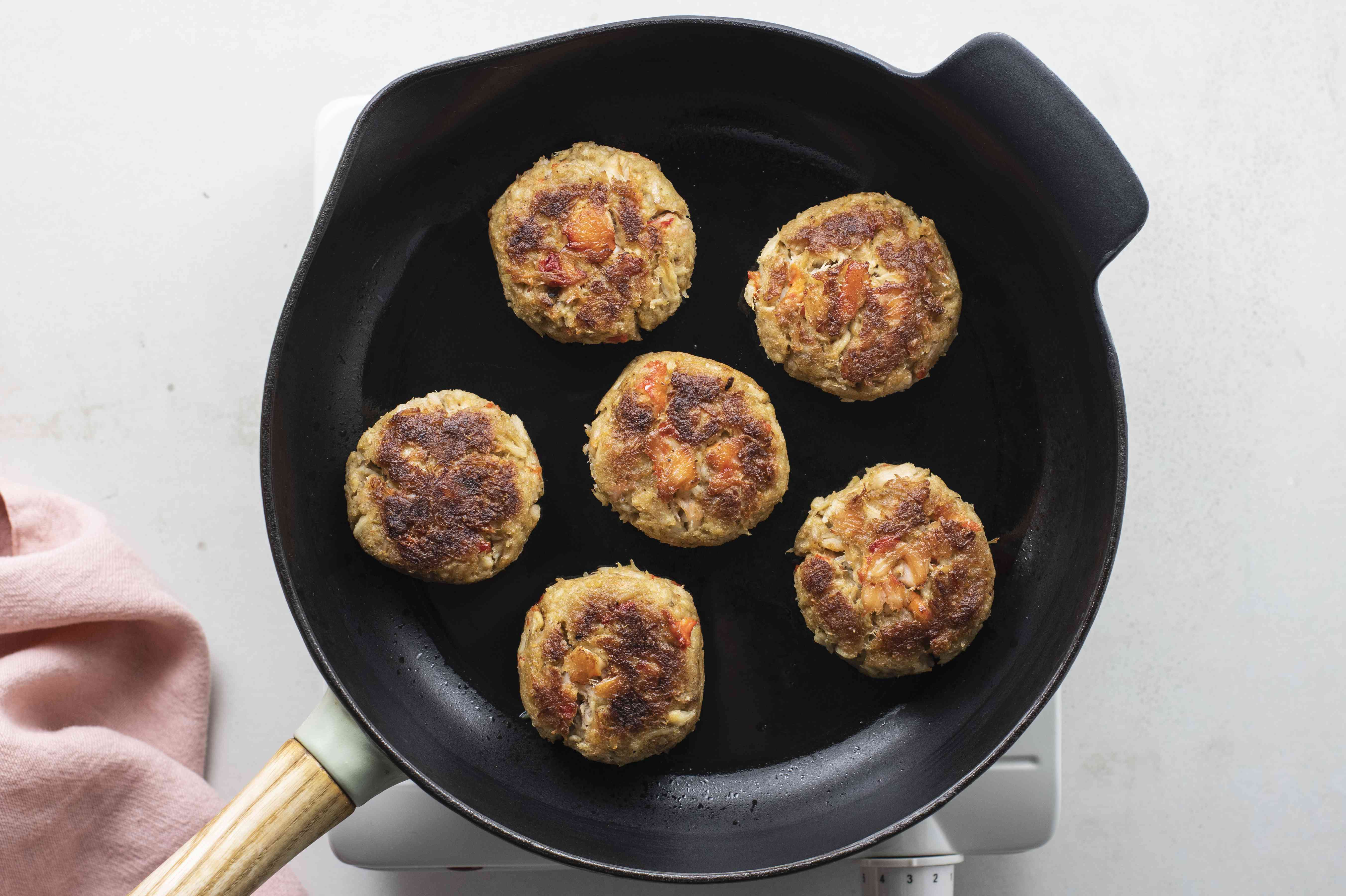 Cooked crab cakes in pan