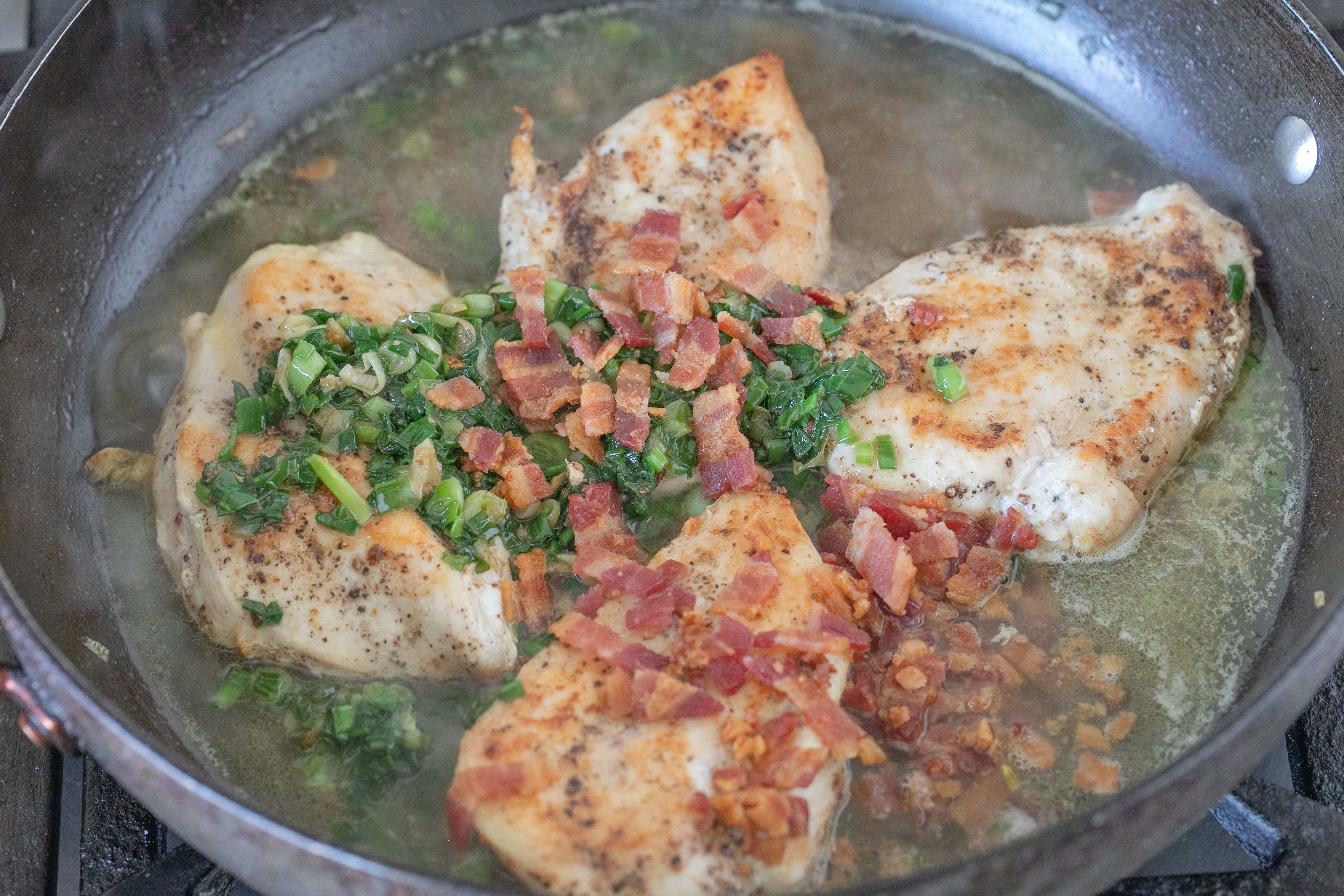 Chicken cooking in broth, green onions and bacon