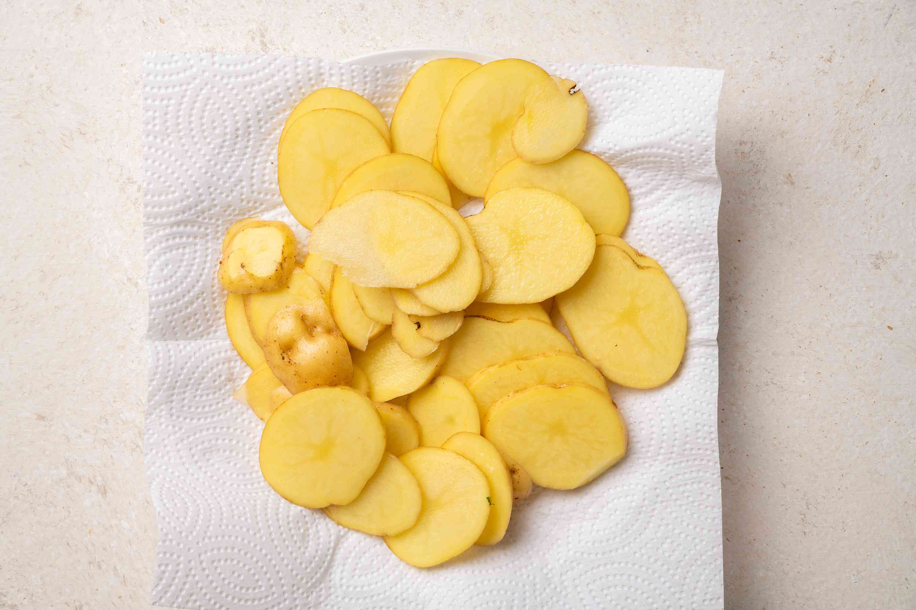 Thinly slice the potatoes and place them on a paper towel