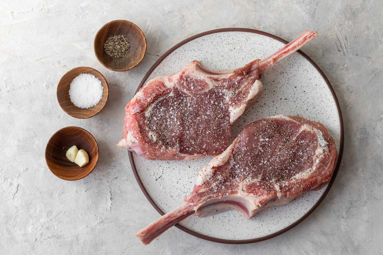 Rub steaks with the cut sides of the garlic and sprinkle with salt and pepper