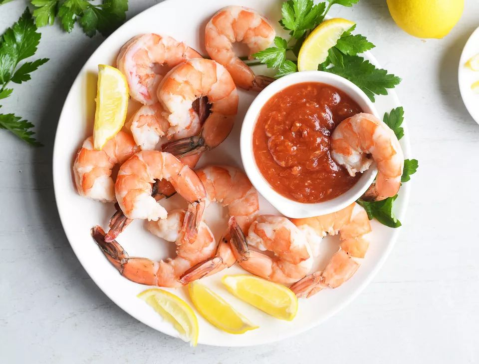 Shrimp cocktail with sauce and lemon wedges