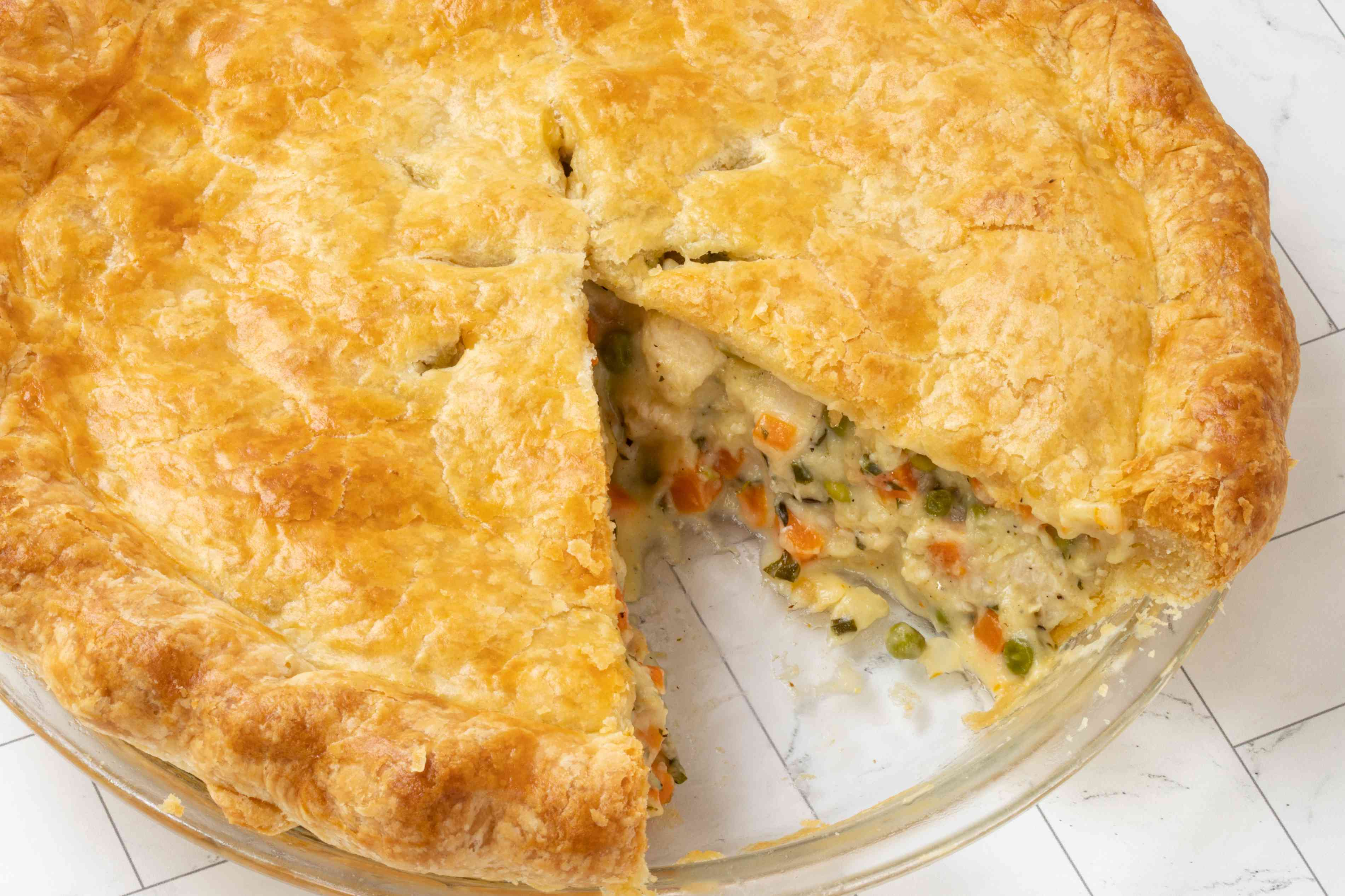 classic chicken pot pie in pie plate with one slice cut out