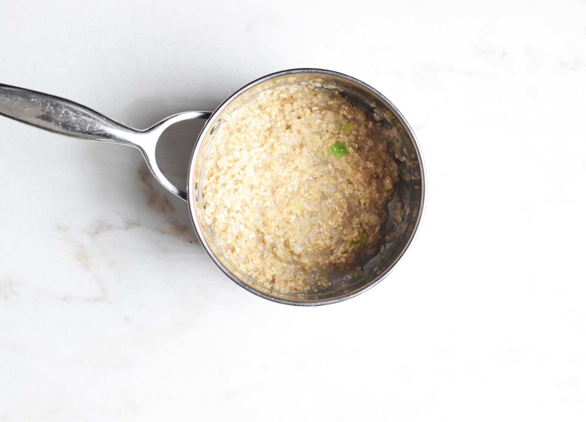 Quick-cooking oats in a saucepan with butter and scallions