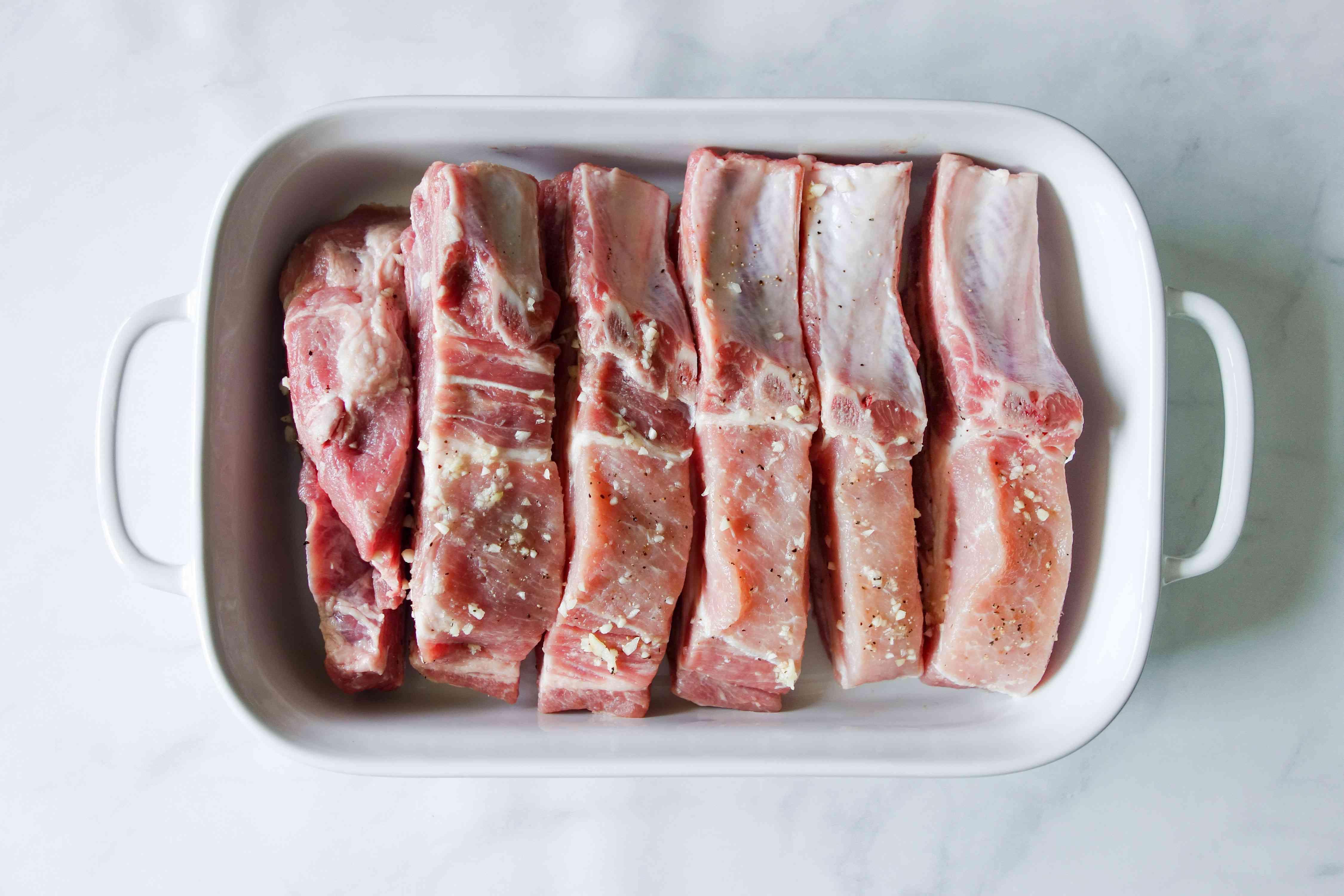 Pork ribs in a roasting pan, meaty-side down