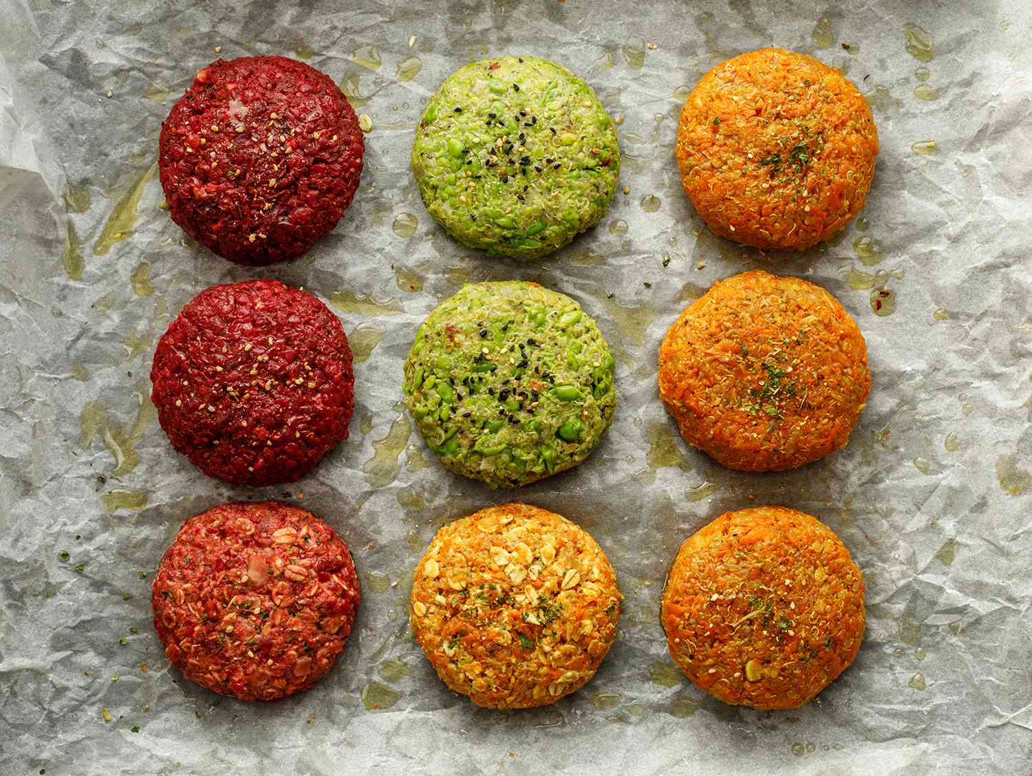Raw vegan burgers made of beetroot, green peas, carrots, groats and herbs on white parchment prepared for baking