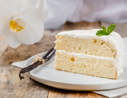 Fluffy vanilla double layer cake on a white plate with a sprig of mint and a vanilla bean