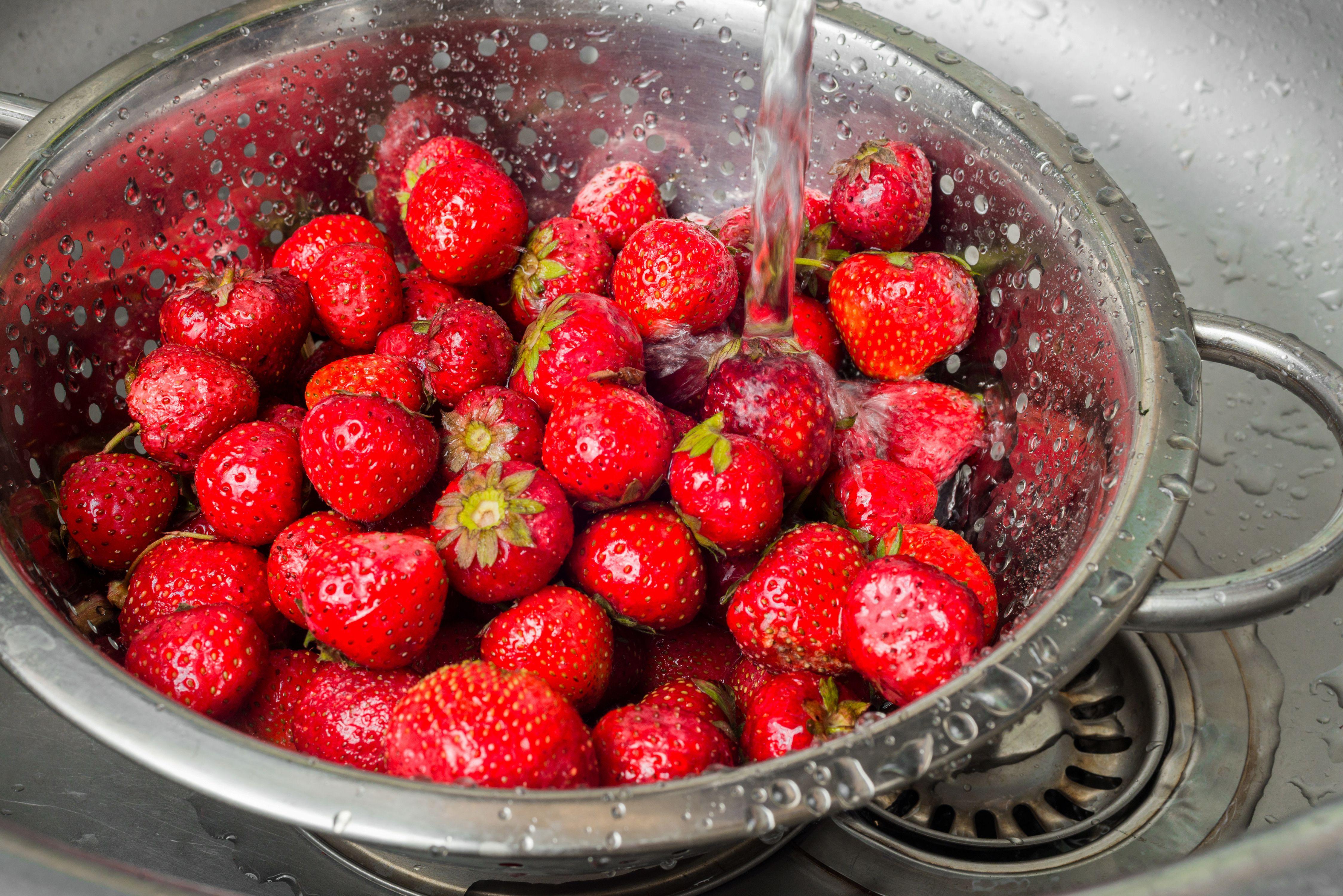 Strawberries being rinsed in a colander