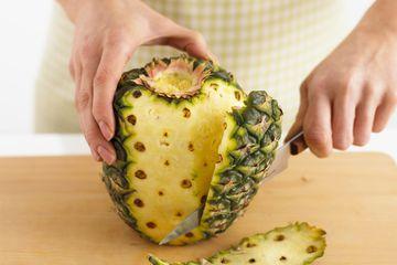 Person peeling pineapple on cutting board