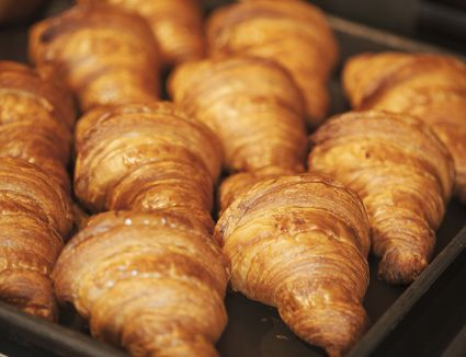 Close up of tray of freshly baked croissants in a bakery.