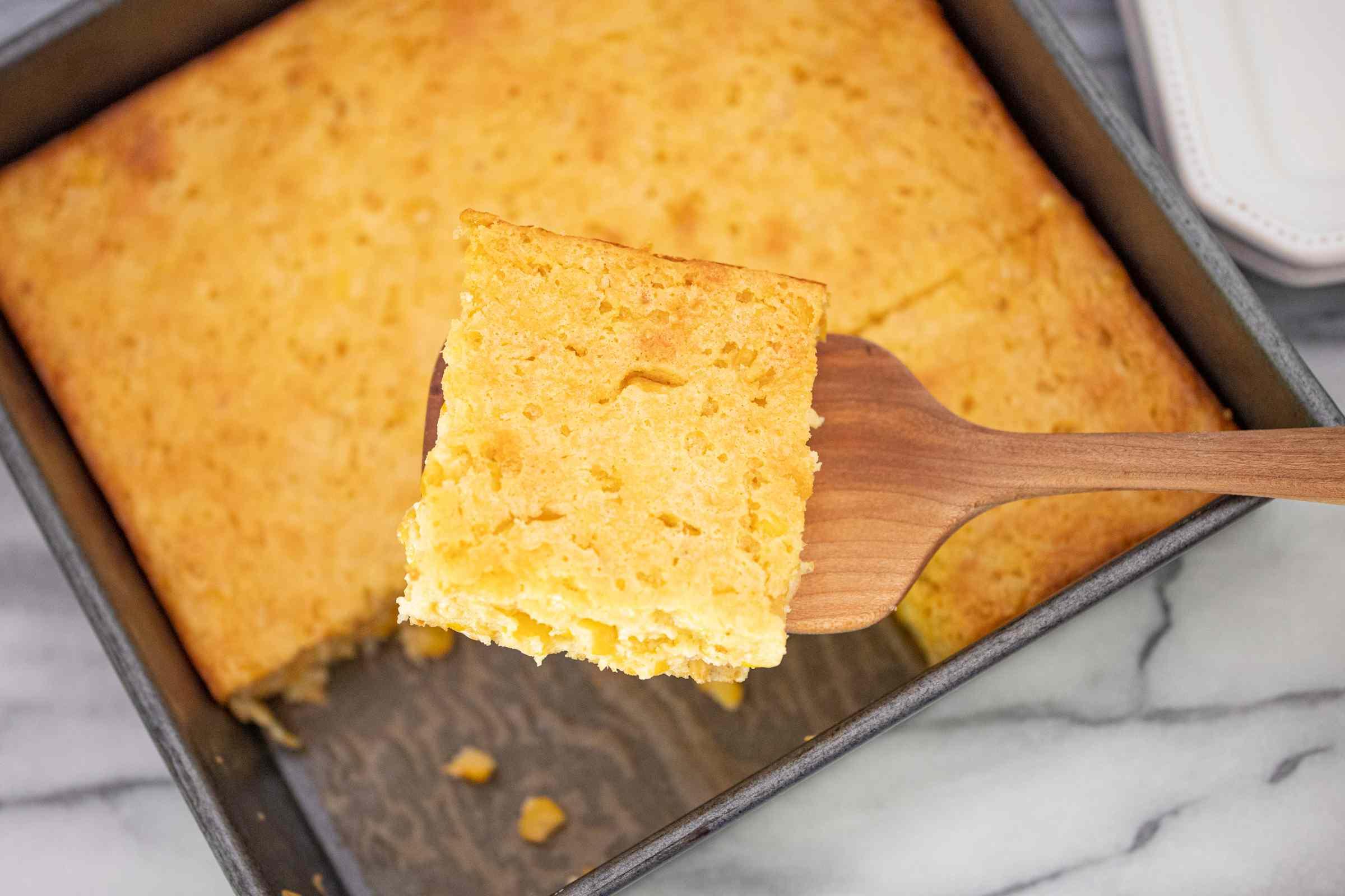 cornbread casserole being taken from pan with spatula