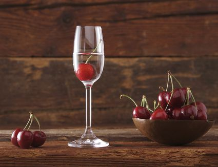 A glass of kirschwasser with cherries in a bowl