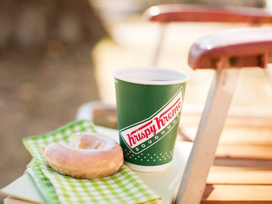 A Krispy Kreme glazed doughnut and a cup of coffee.