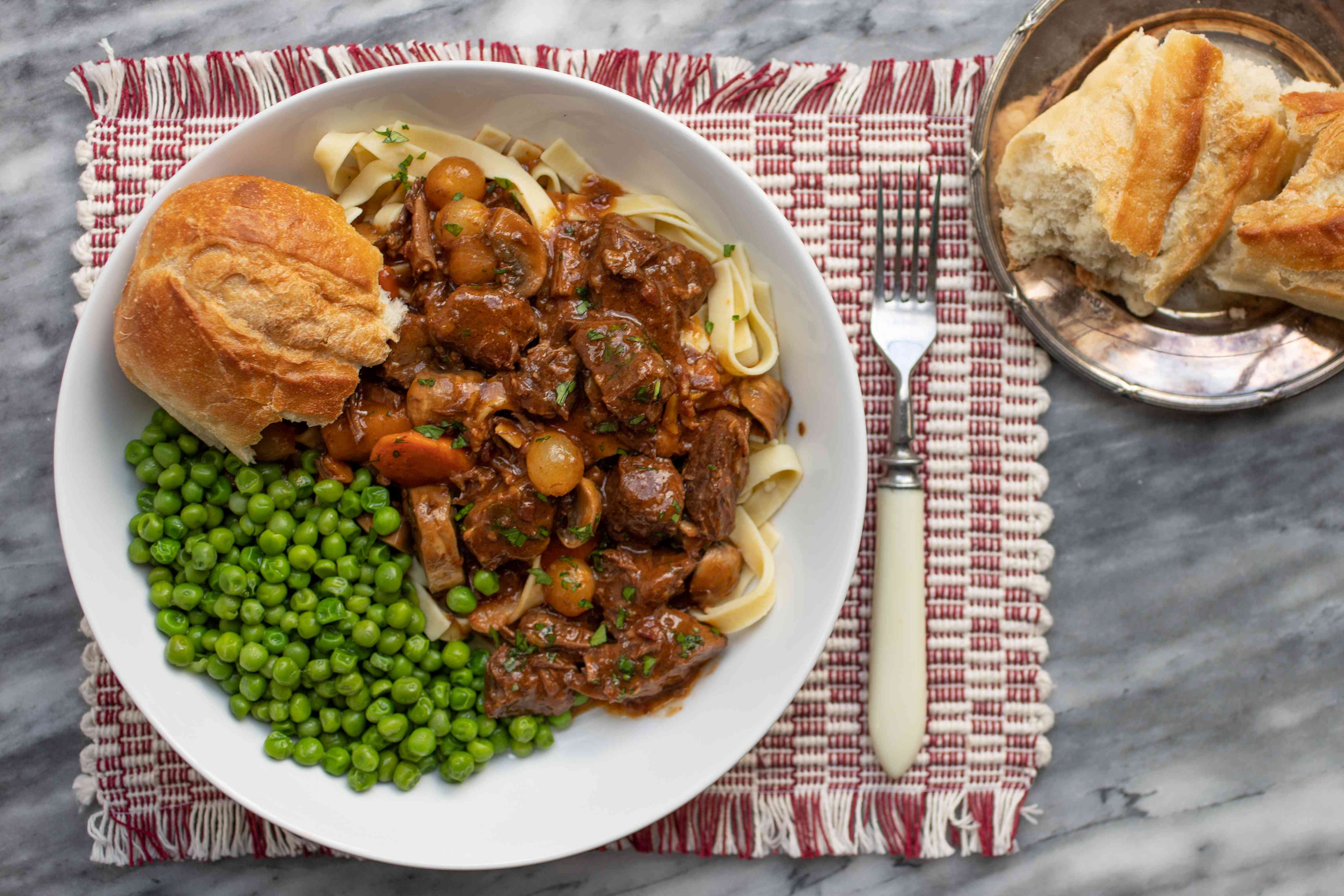 instant pot beef bourguignon in a serving dish with french bread