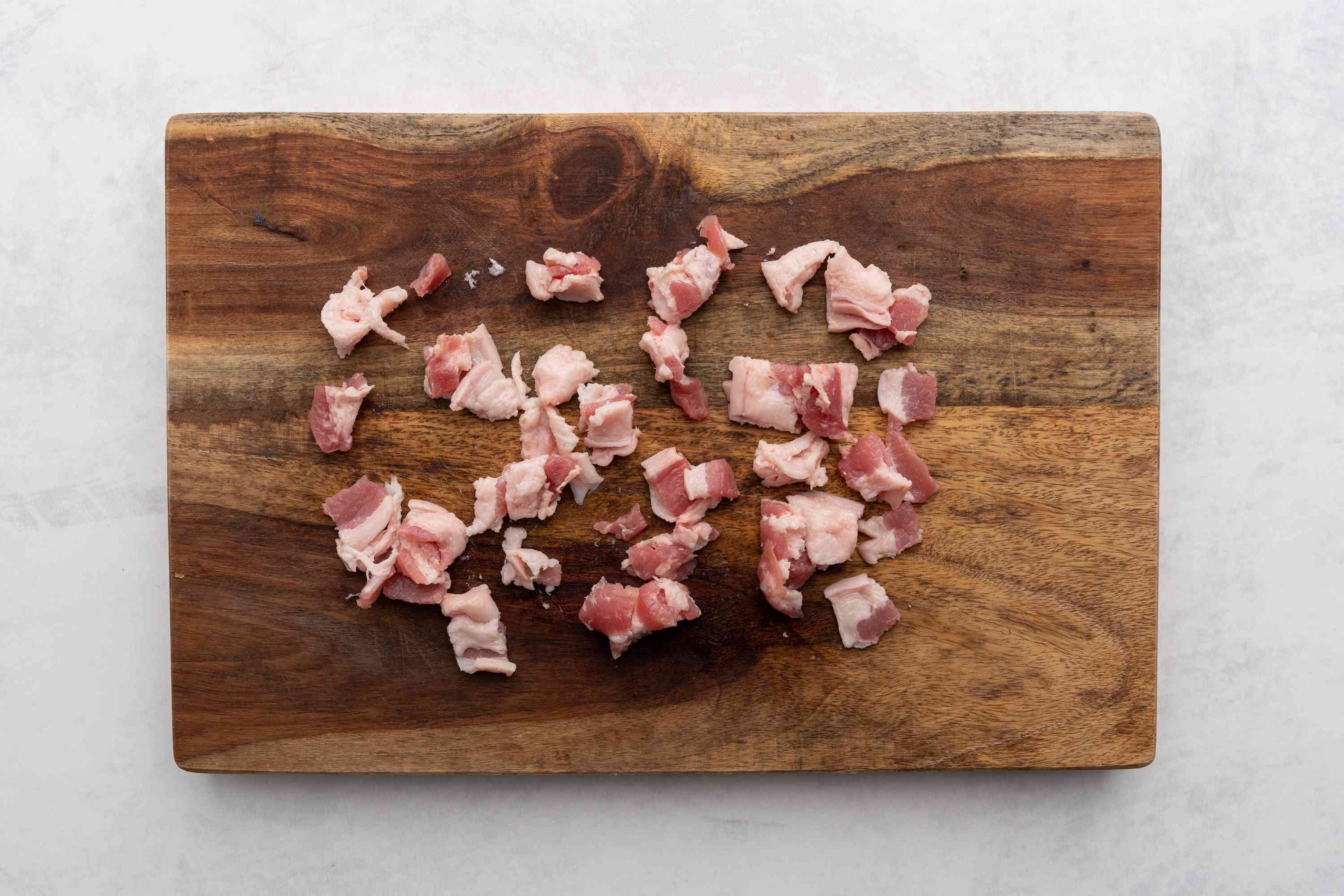 bacon cut into pieces on a cutting board