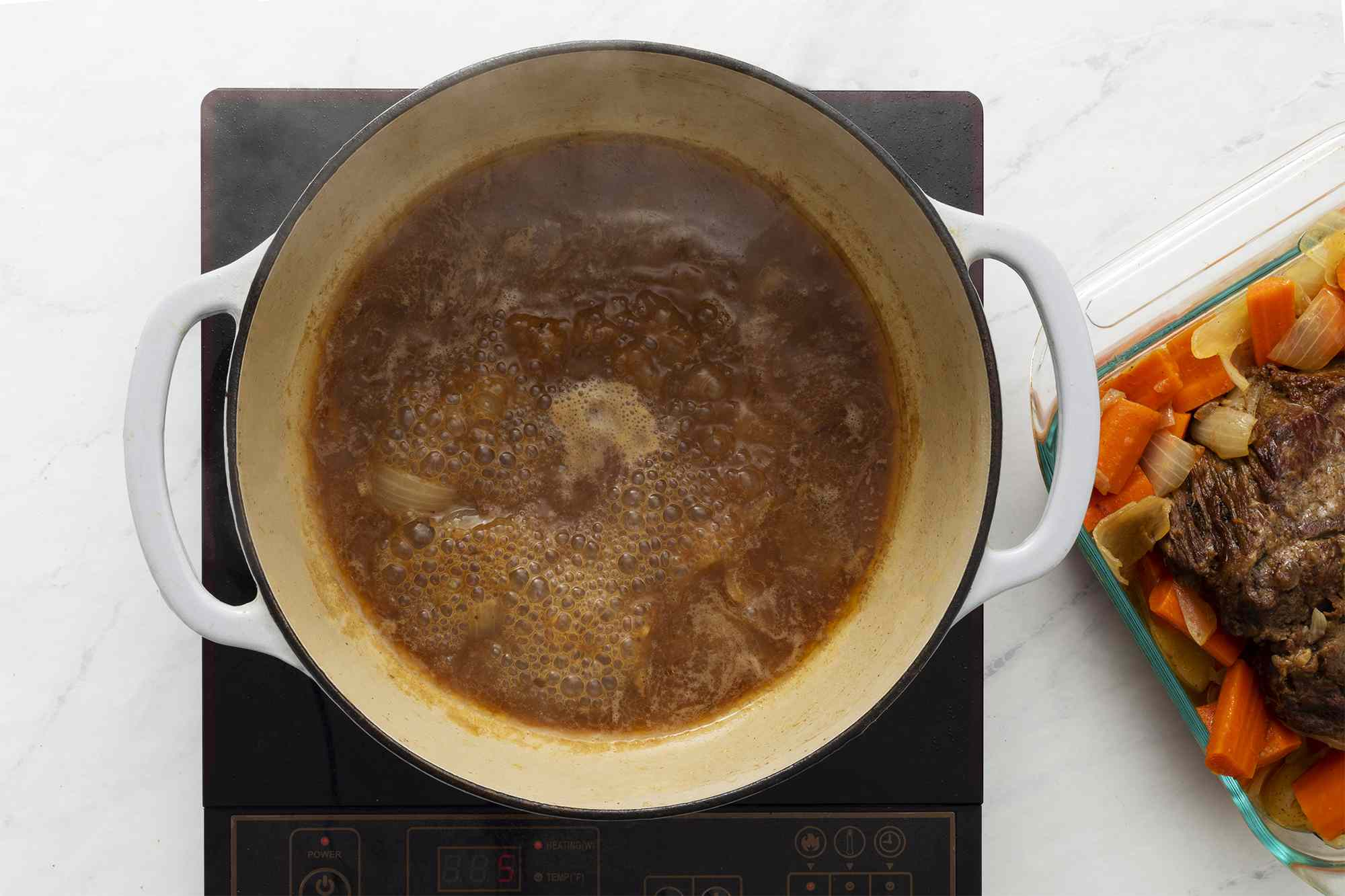 pot roast and vegetable removed from the Dutch oven, stock remains in the Dutch oven