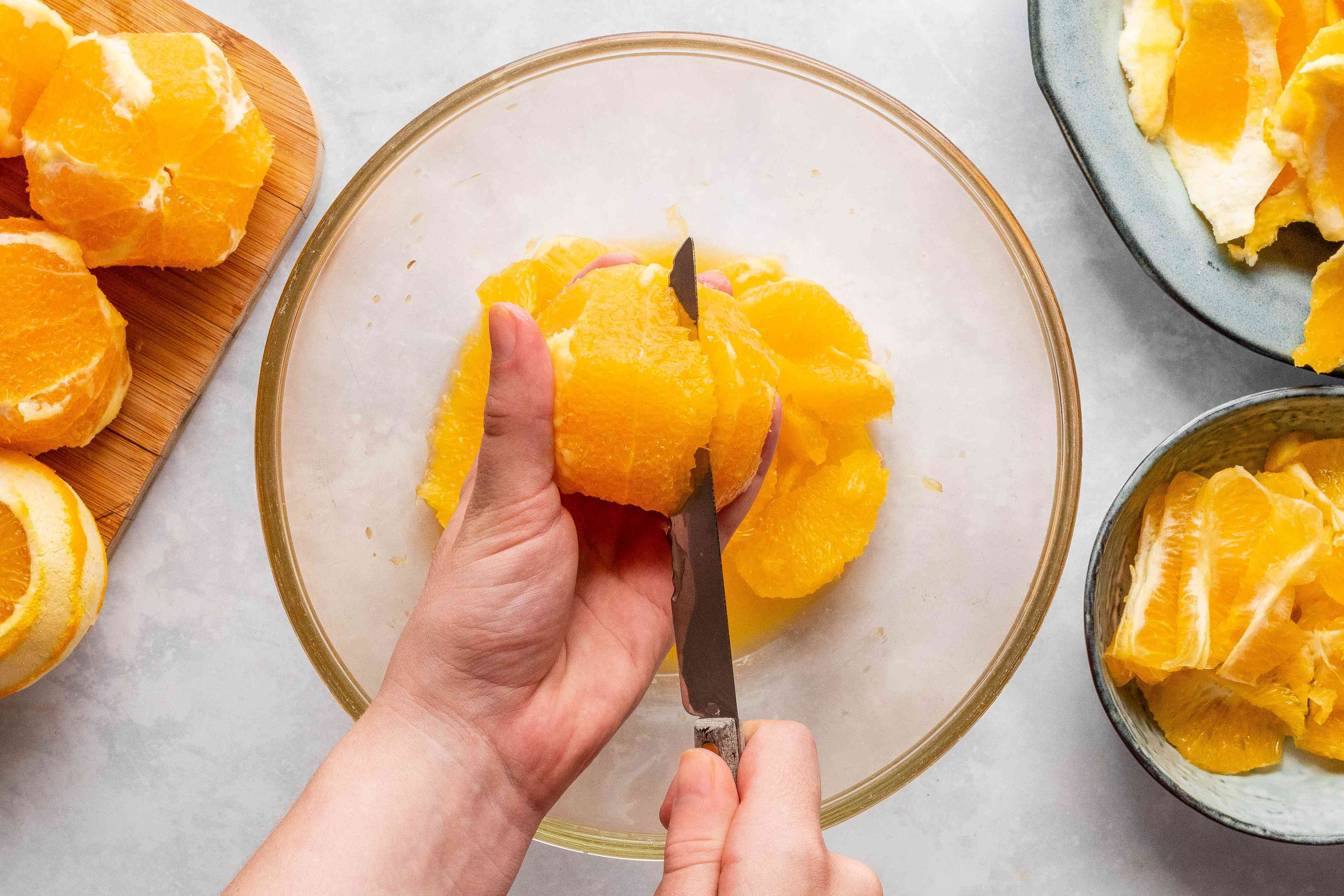 cutting out orange segments with a knife, into a glass bowl