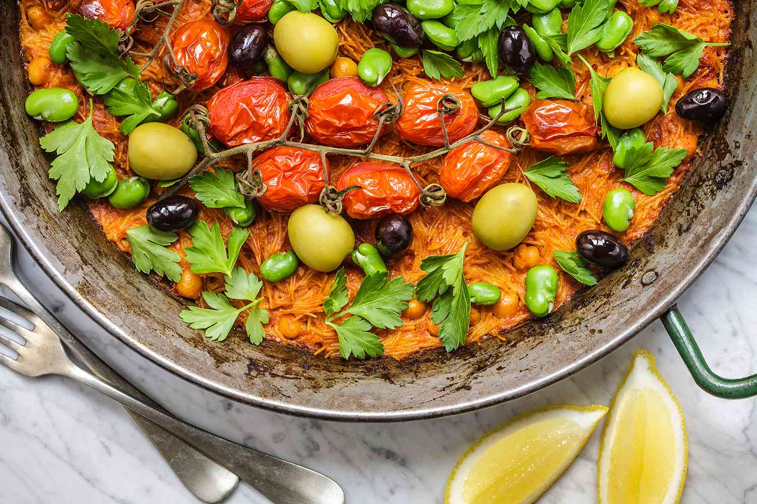 This traditional Catalan dish of baked noodles has been modernised with chickpeas, vine roasted tomatoes, olives and peeled fava beans. Accompanied with garlic alioli and lemon wedges, ready for Sunday lunch.