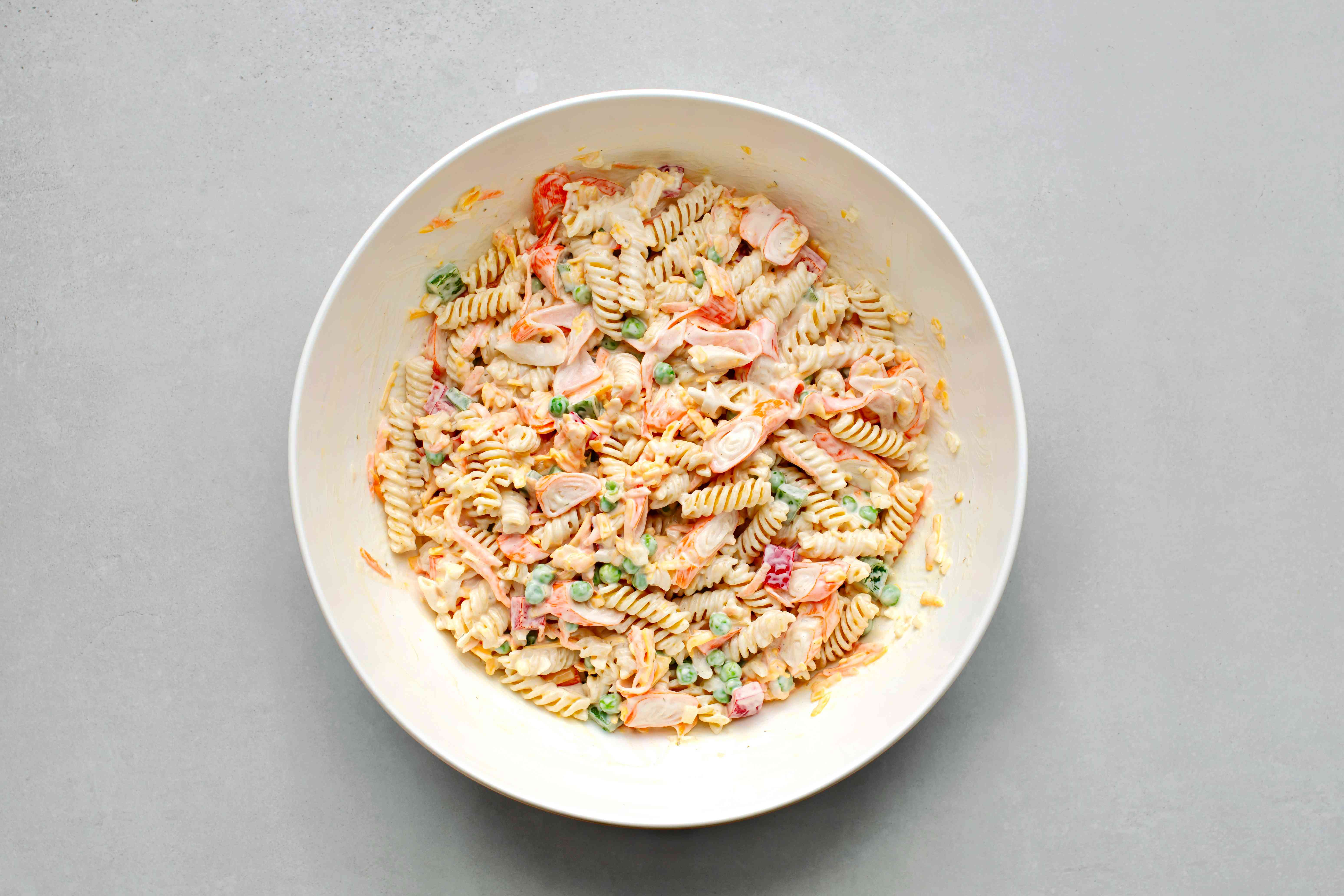 pasta along with seafood, shredded cheese, ranch dressing, peas, green and red bell pepper, onion, and carrot in a bowl
