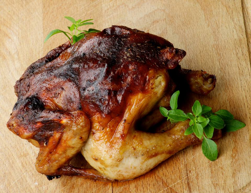 Glazed rotisserie chicken on cutting board