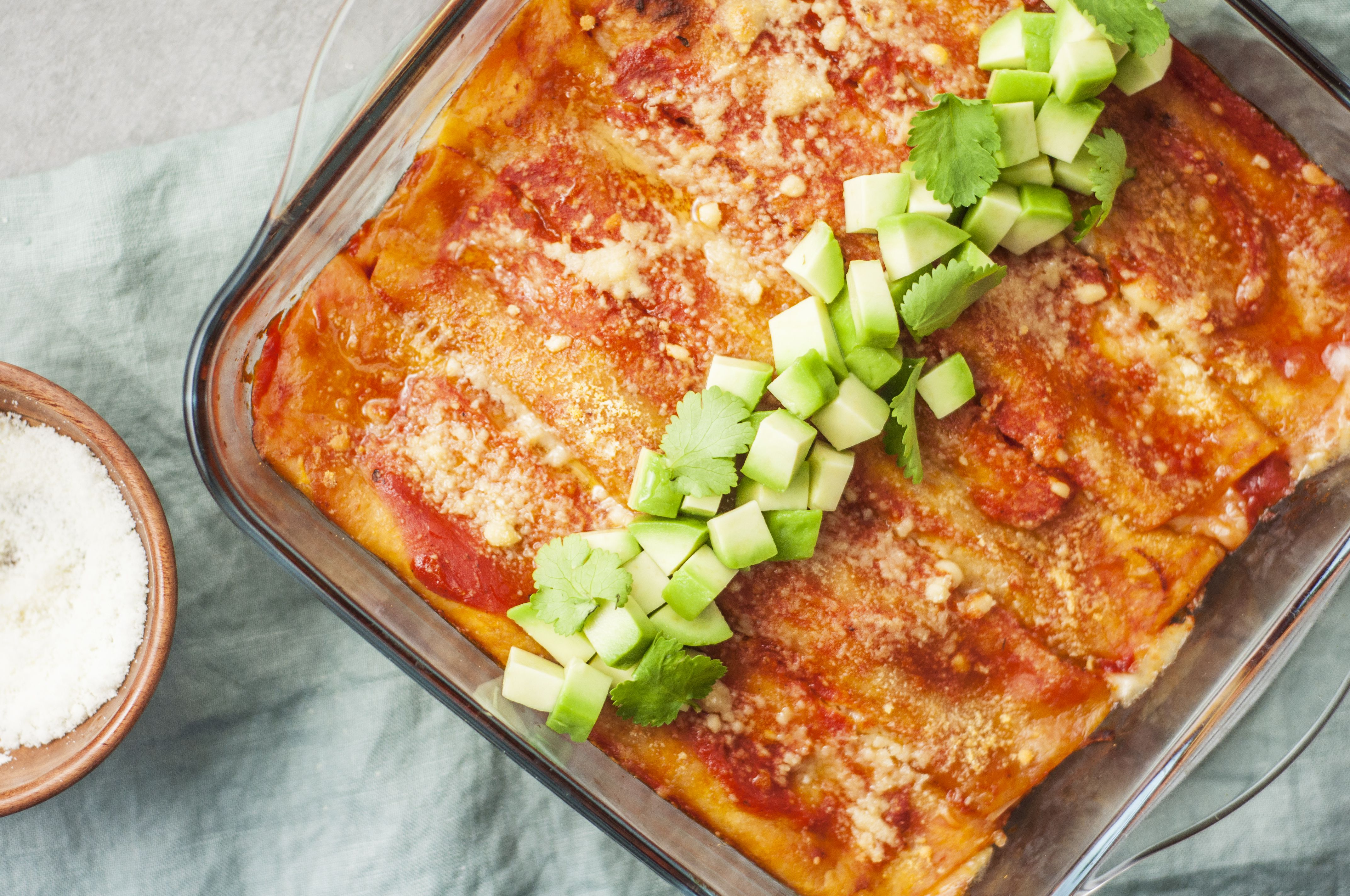 Cheese enchiladas baked and topped with cilantro and avocado