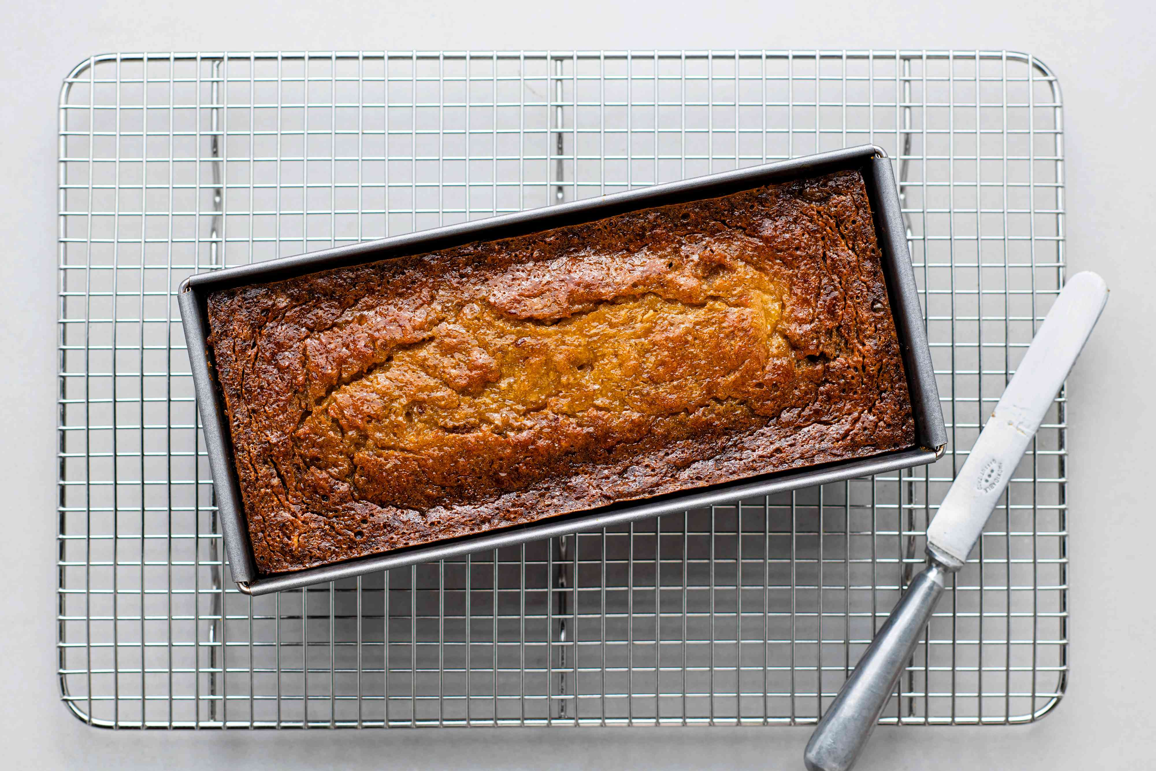 Easy Persimmon Quick Bread in a loaf pan on a drying rack