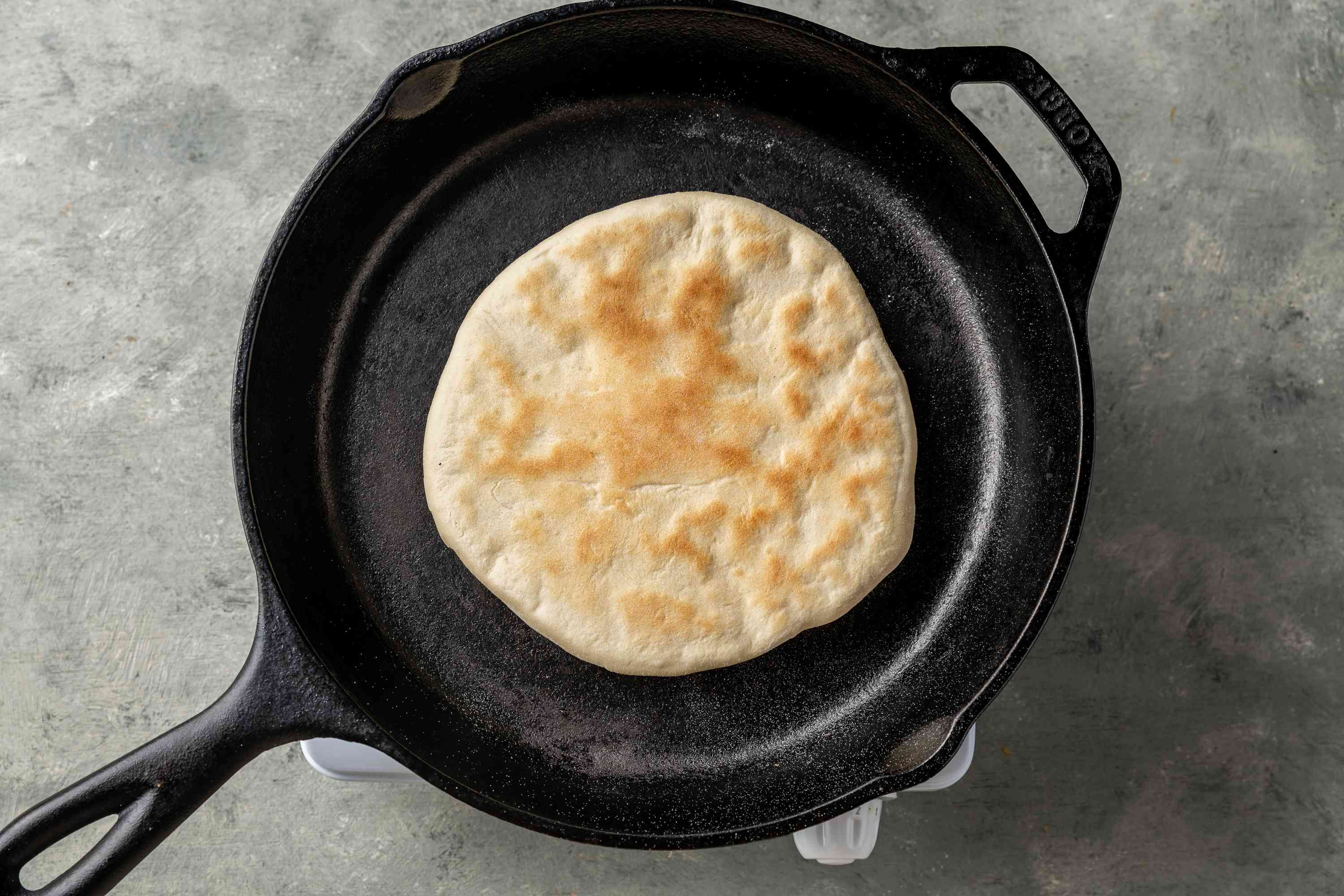 roti cooking in a cast iron skillet